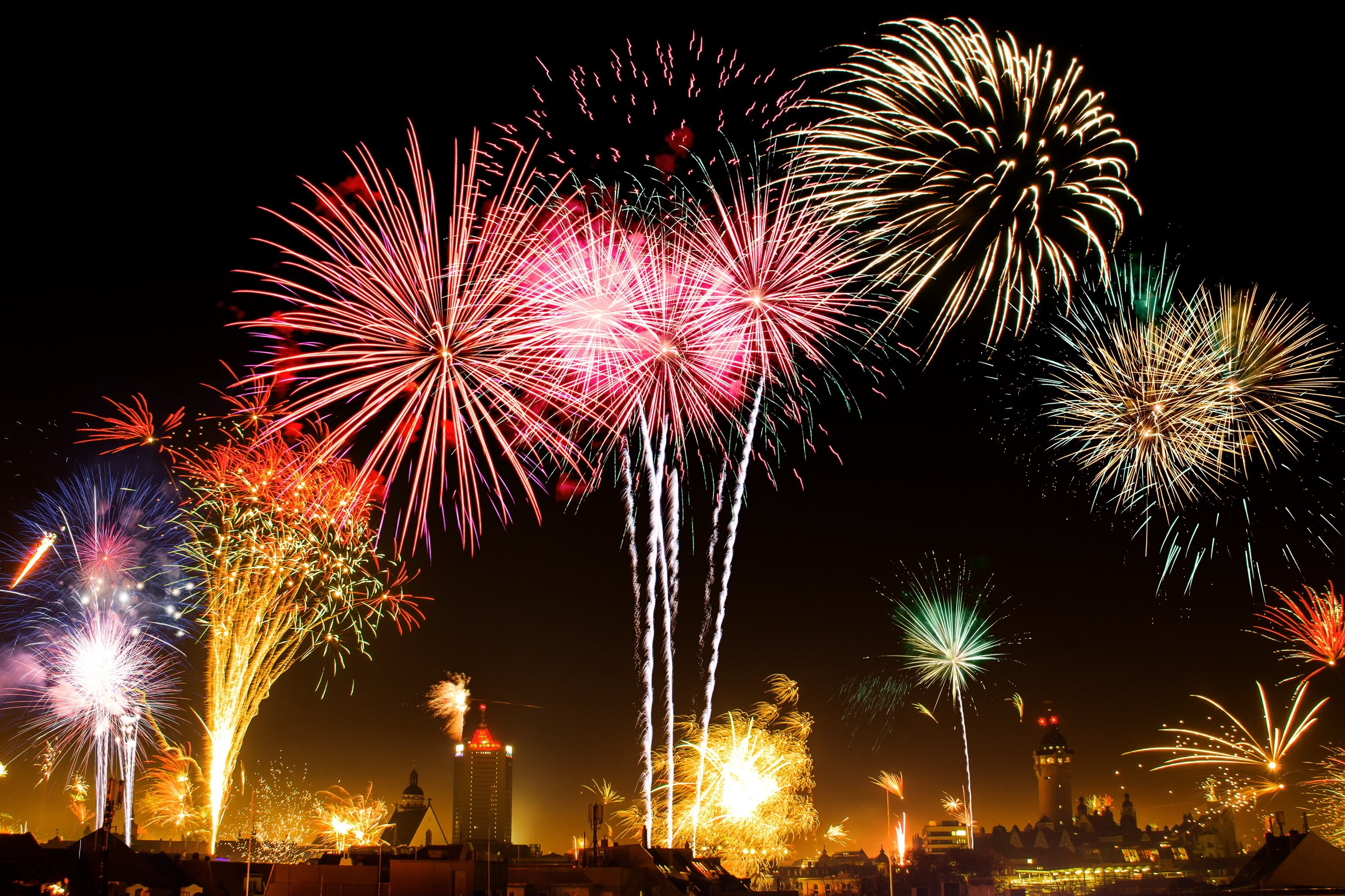 Multiple colour fireworks exploding in the sky with skyscrapers in the background