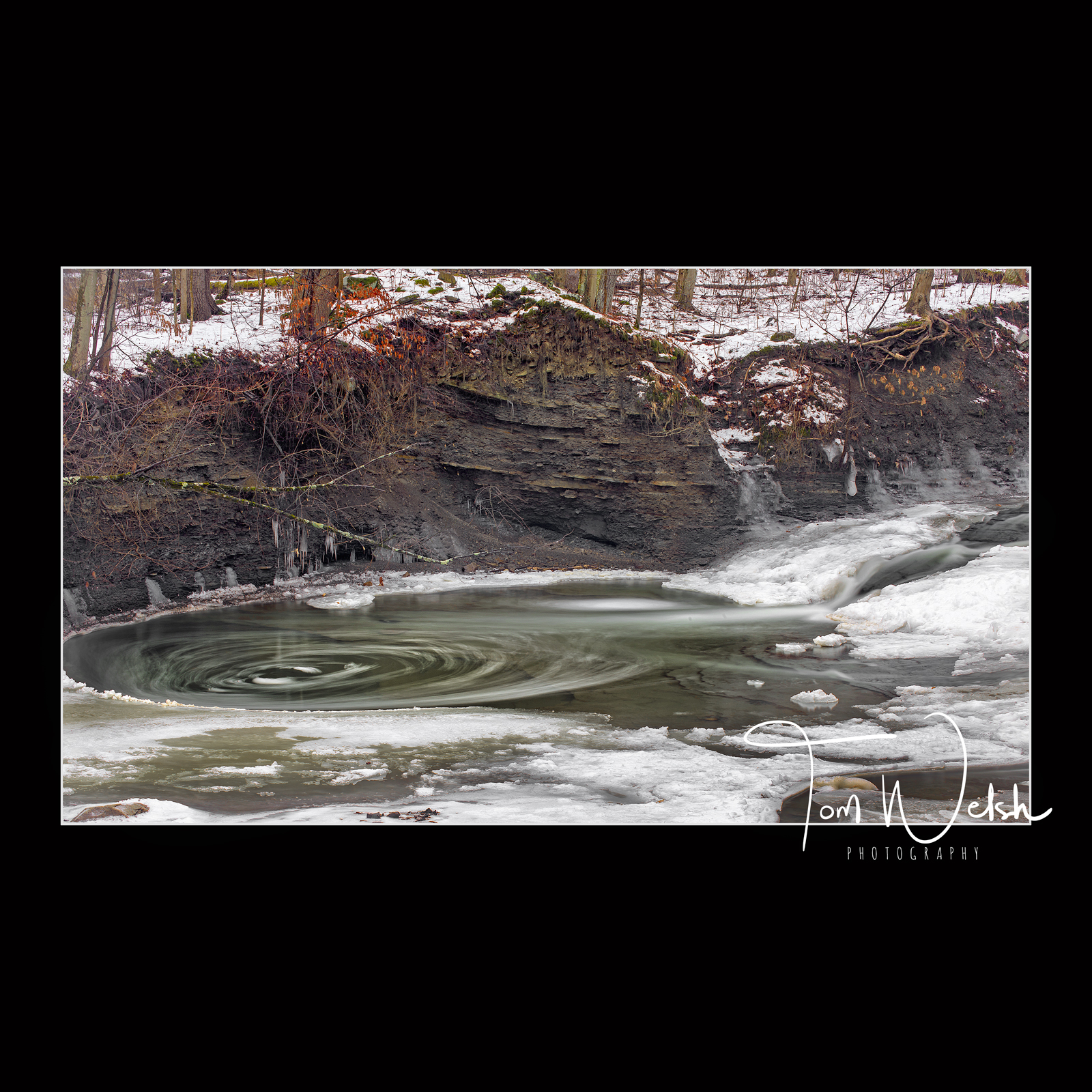 Water swirls as it tries to escape the frozen pool along the stream bed below the falls