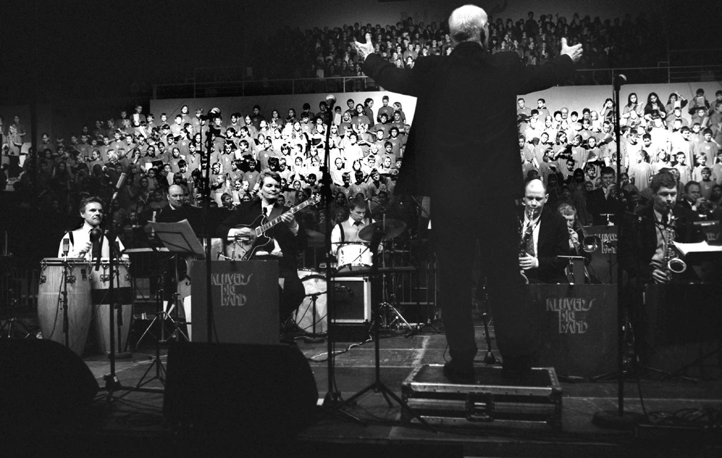 Jens Klüver dirigerer bigband og små 1500 skoleelever under årets kæmpekor i Ceres Arena, 2004.