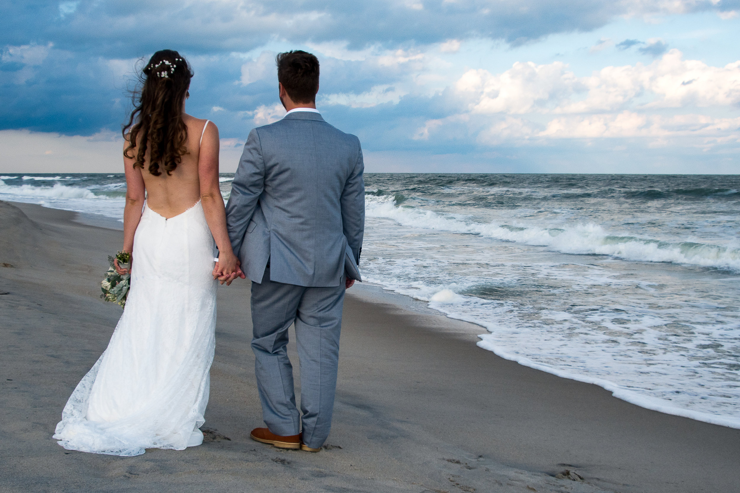 - Holding hands watching the clouds over the beach and reflecting on their new life together after the beach wedding ceremony.