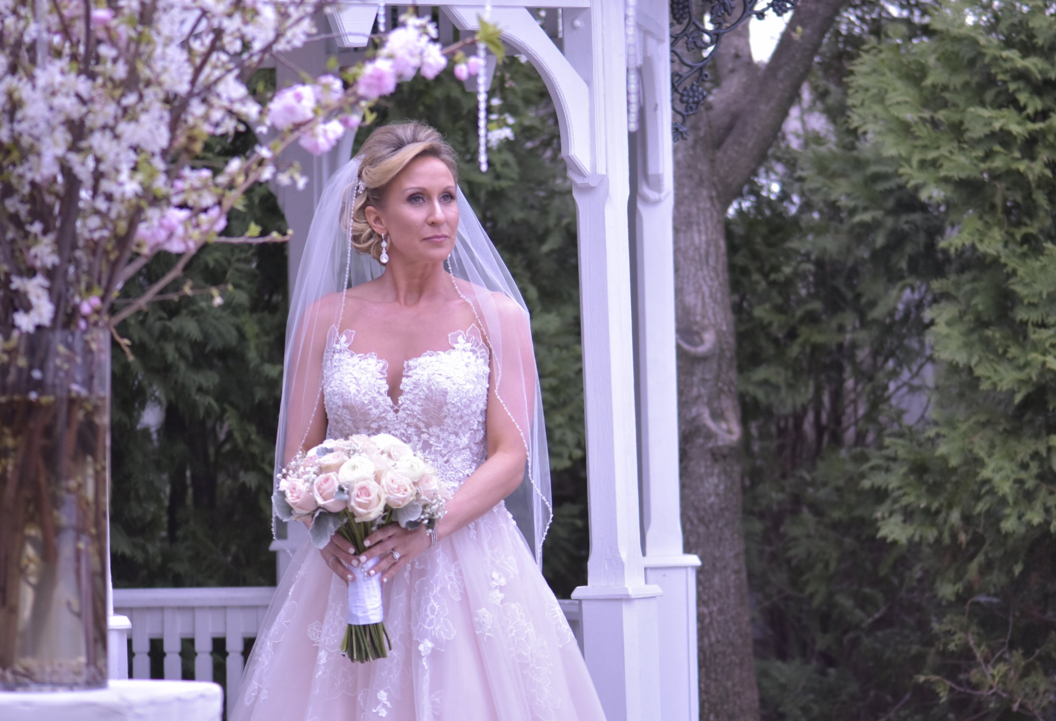 - A brides gaze as she is holding her bouquet of pink roses.