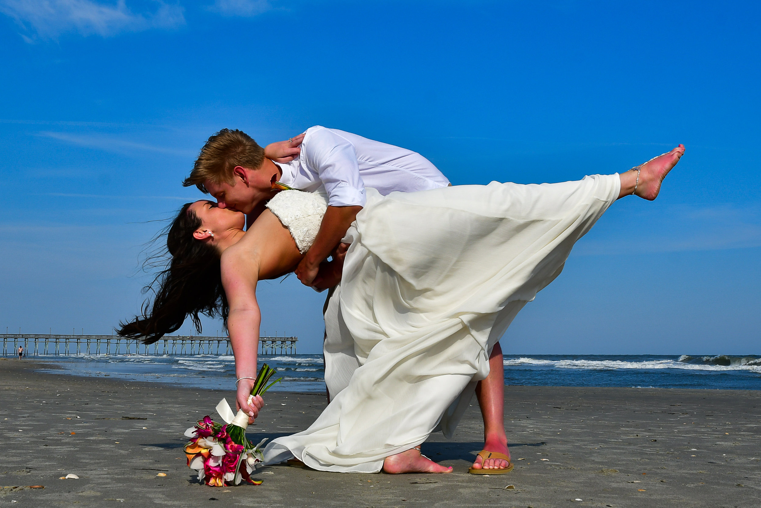 - Classic pose of groom dipping bride on the beach at waters edge with pier in the background.