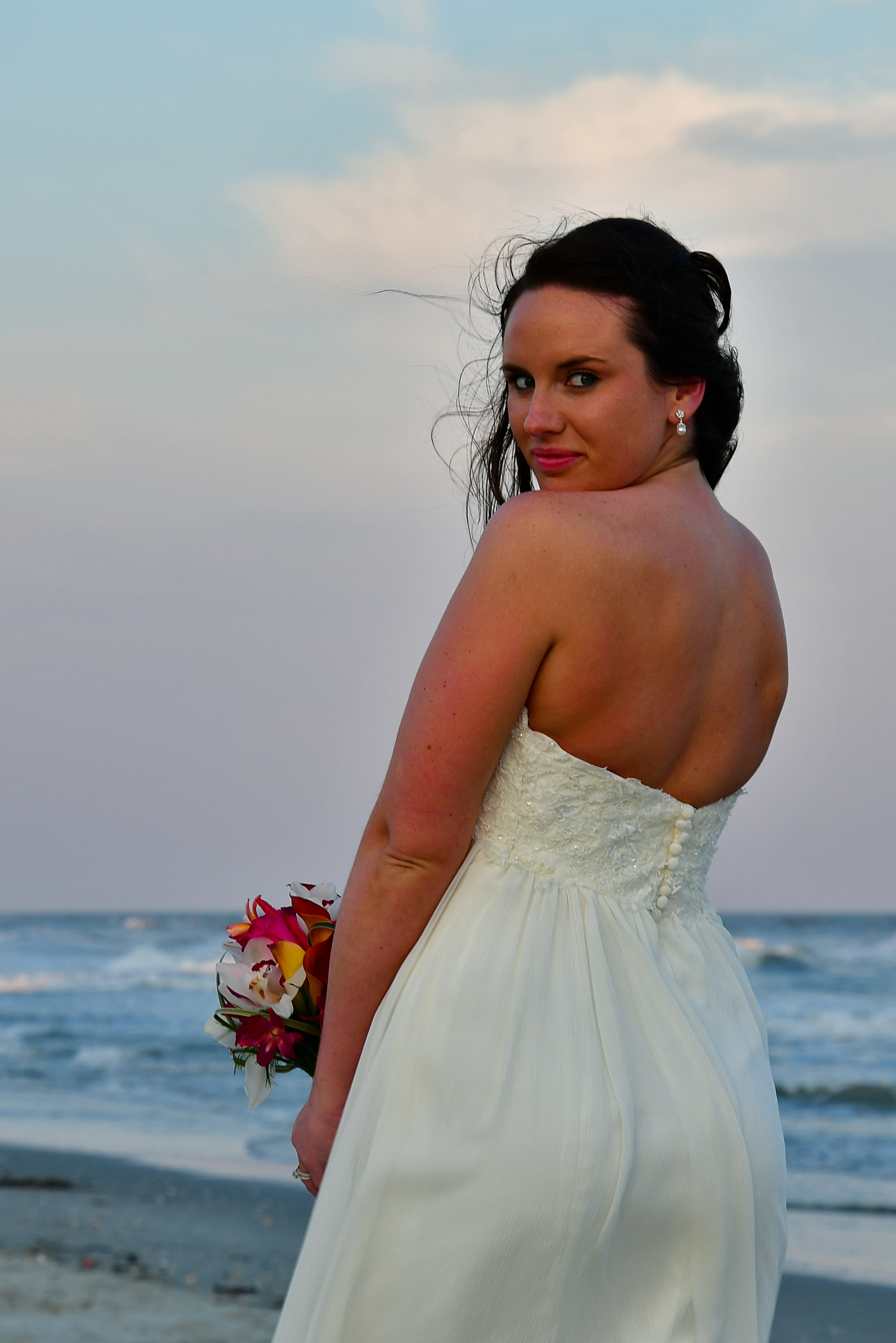 - Bride standing on the beach holding bouquet looking back at the camera.