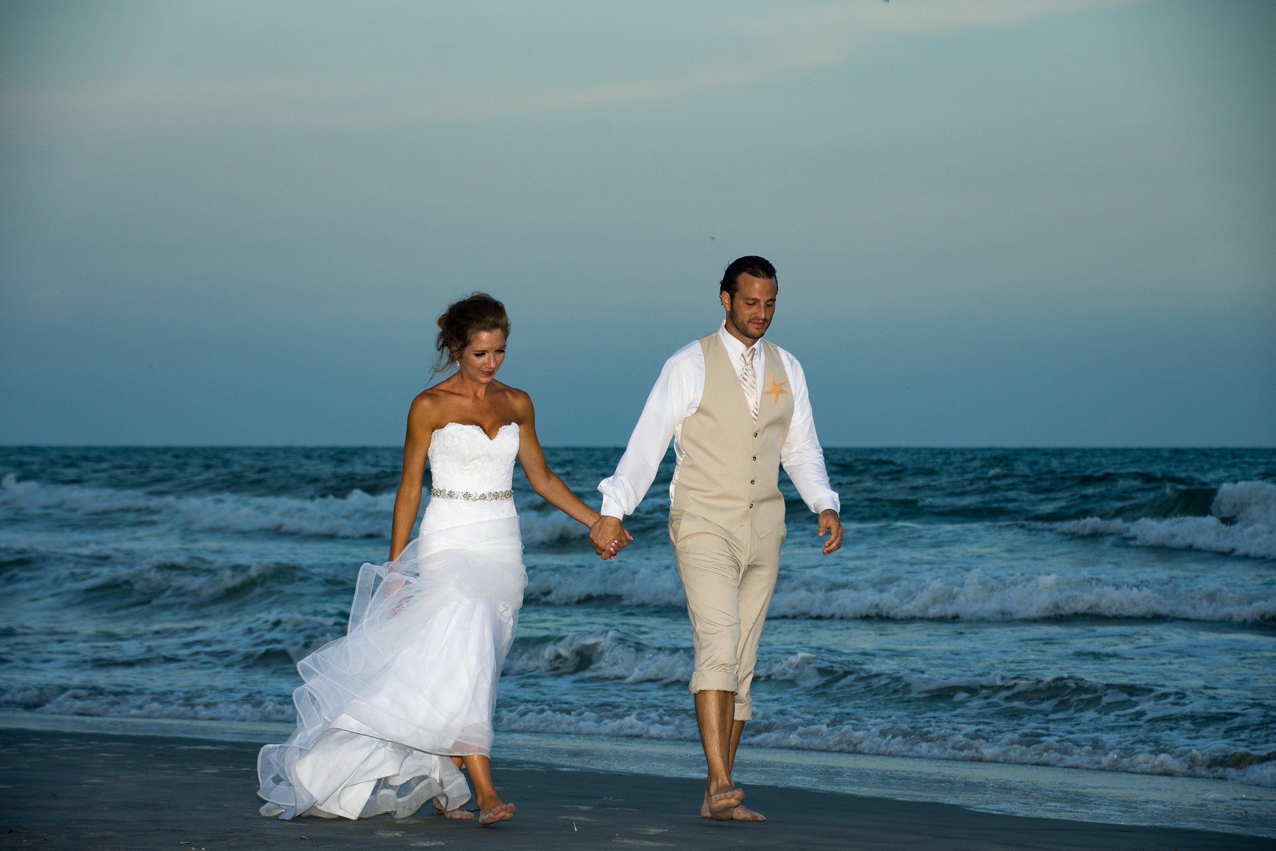 - Bride and groom walking at waters edge holding hands after ceremony.