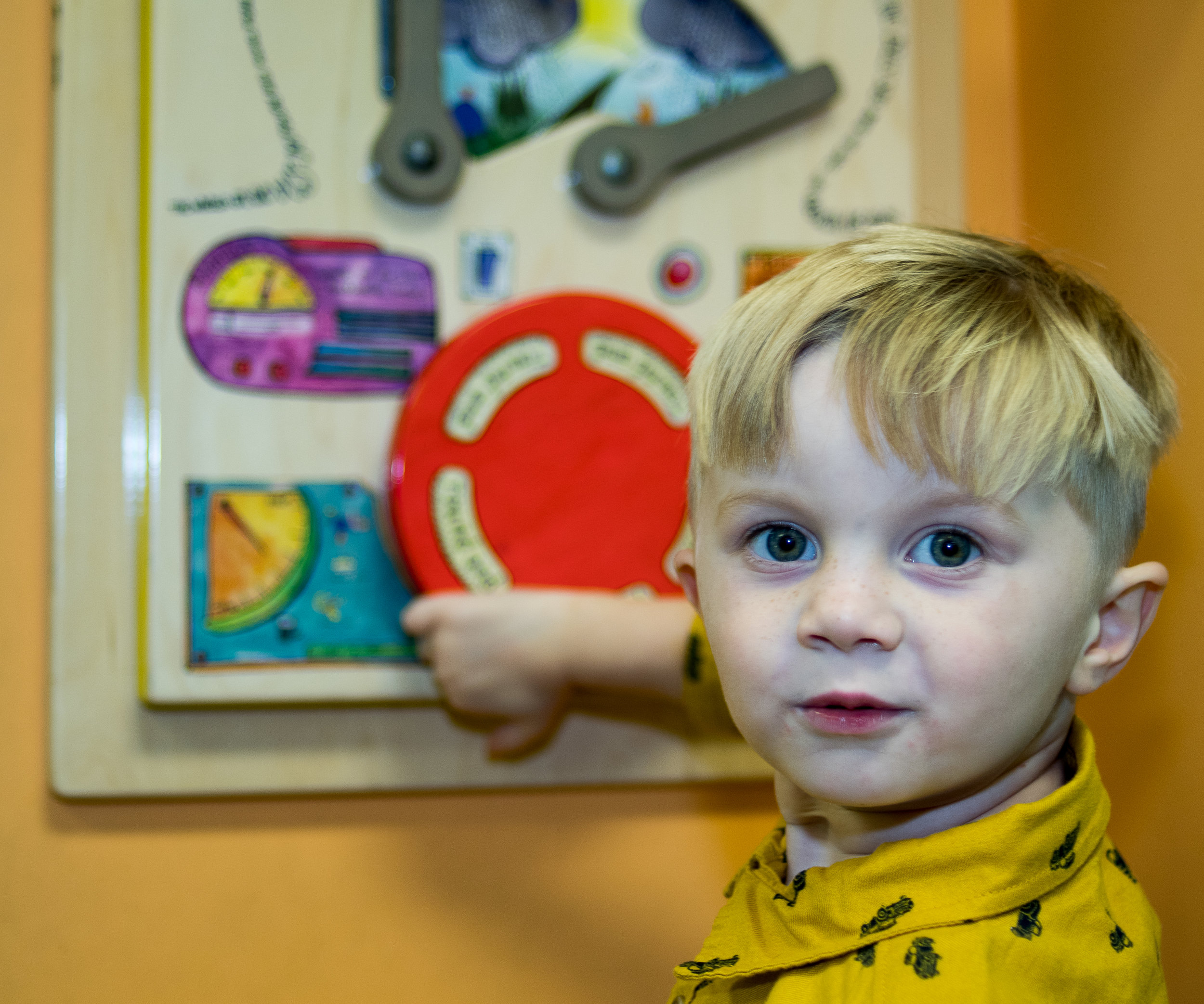 - Young boy turning red mechanical wheel inside Wilmington's Downtown Library.