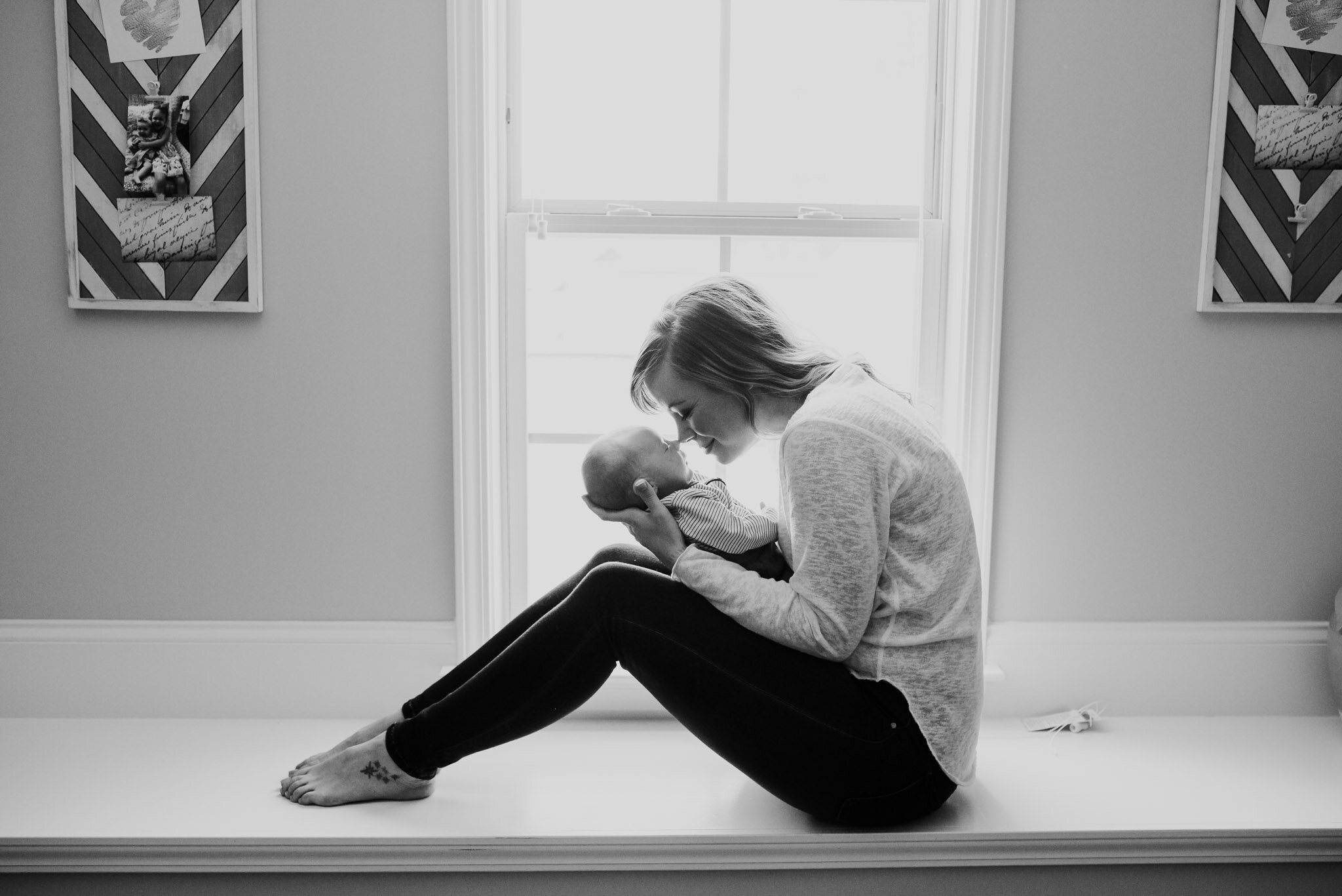 Mom holding newborn baby in front of window