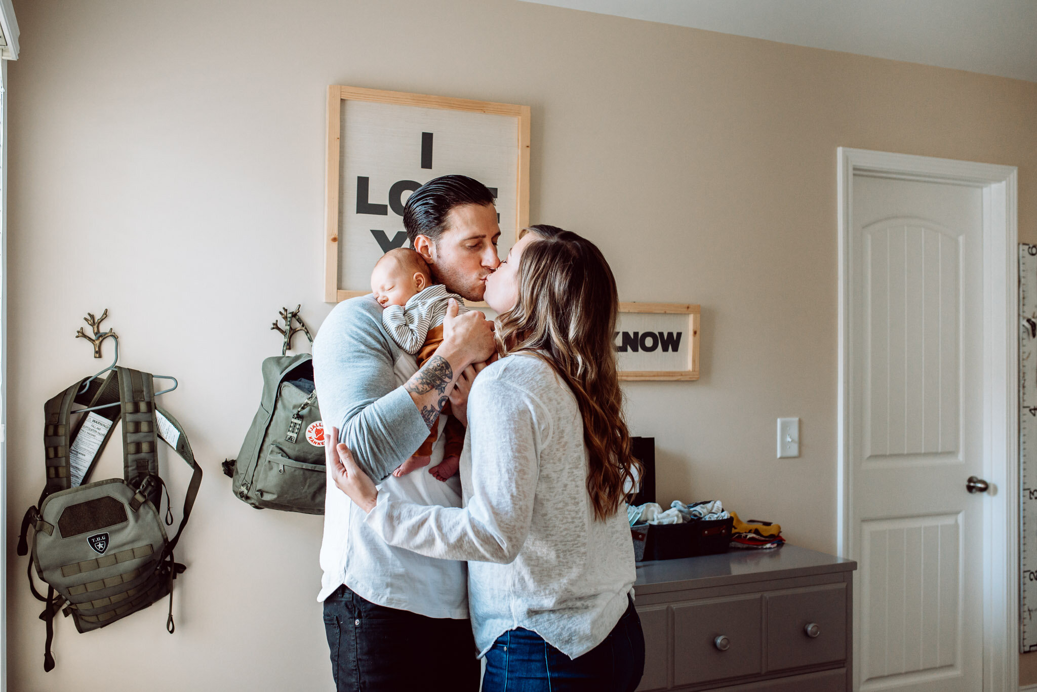 Mother Father kissing while holding newborn