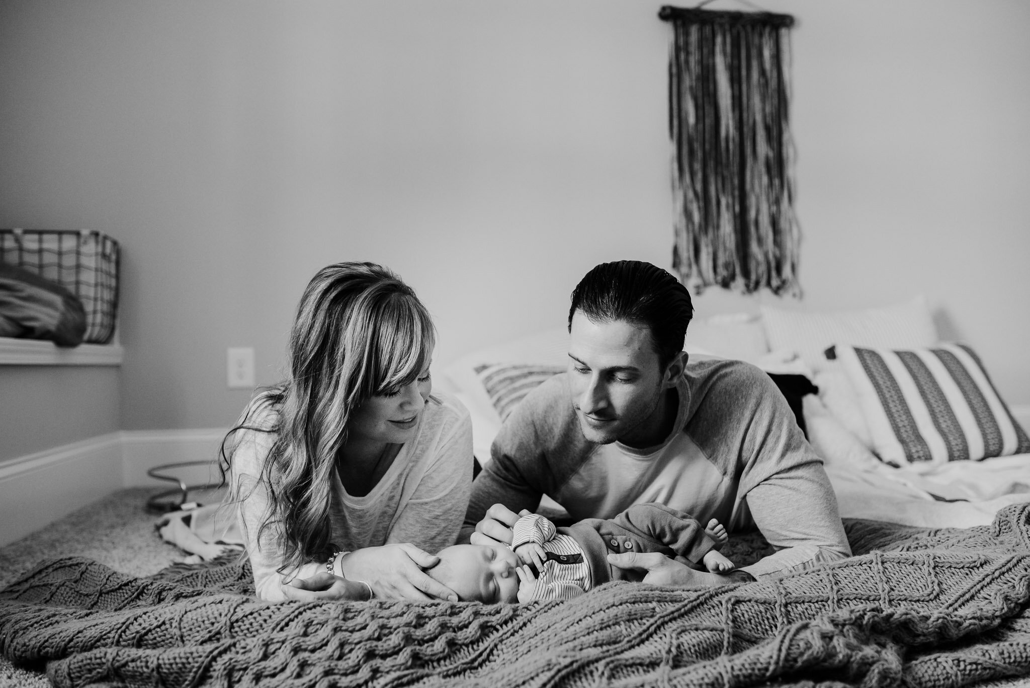 Parents looking at baby on blanket