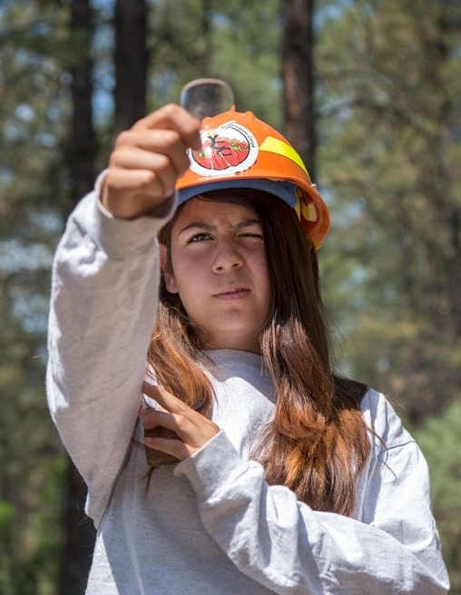 Raelynn Archuleta, 18, of El Rito uses a prism to determine which trees are within a plot she and others are collecting data about in El Rito Ranger District.  Eddie Moore/Albuquerque Journal