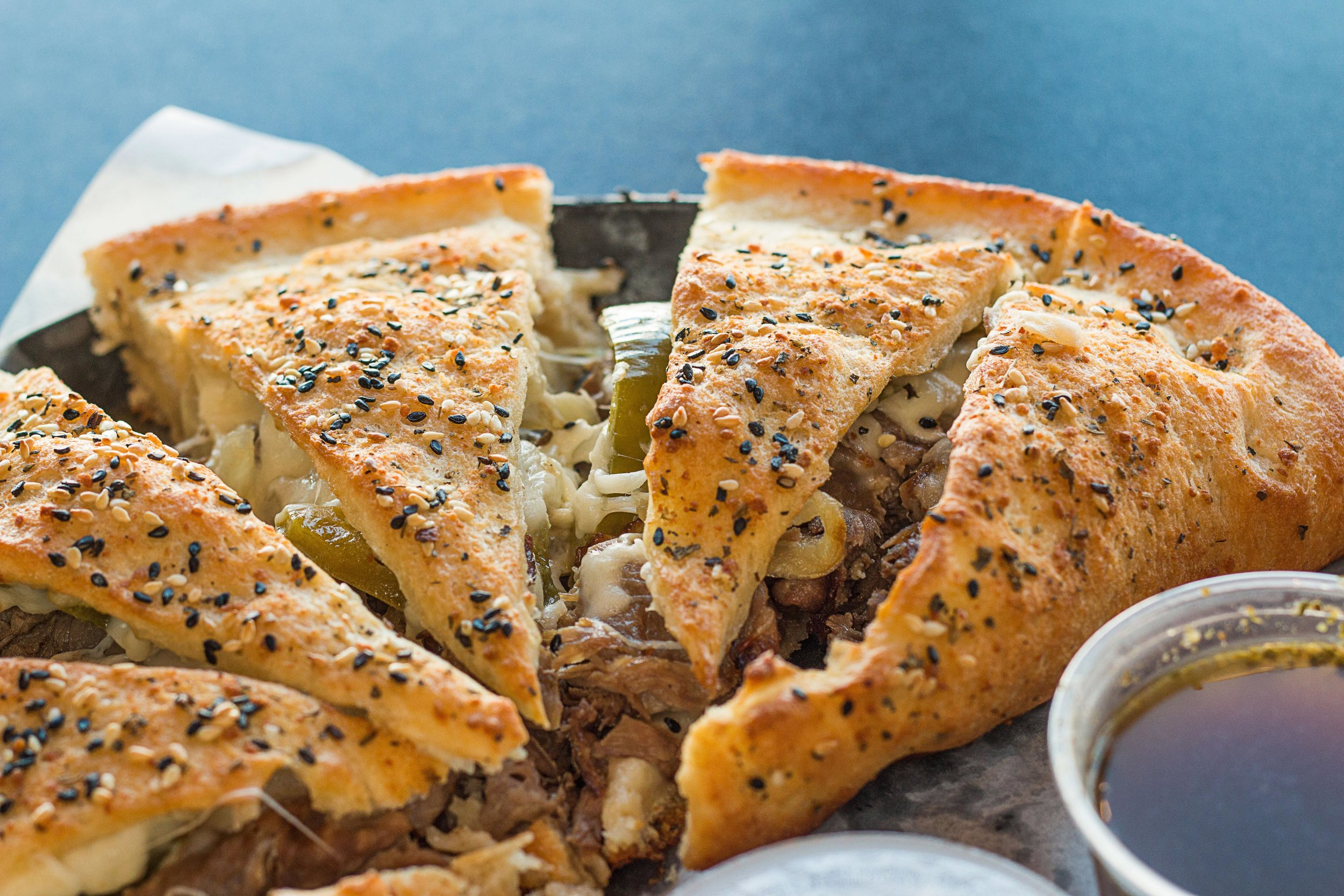 Chicago Beef Calzone- Prepared with our freshly made pizza dough then stuffed with Chicago-Style Beef, onions, bell peppers, cheese, & giardiniera. Served with 3 different dipping sauces!