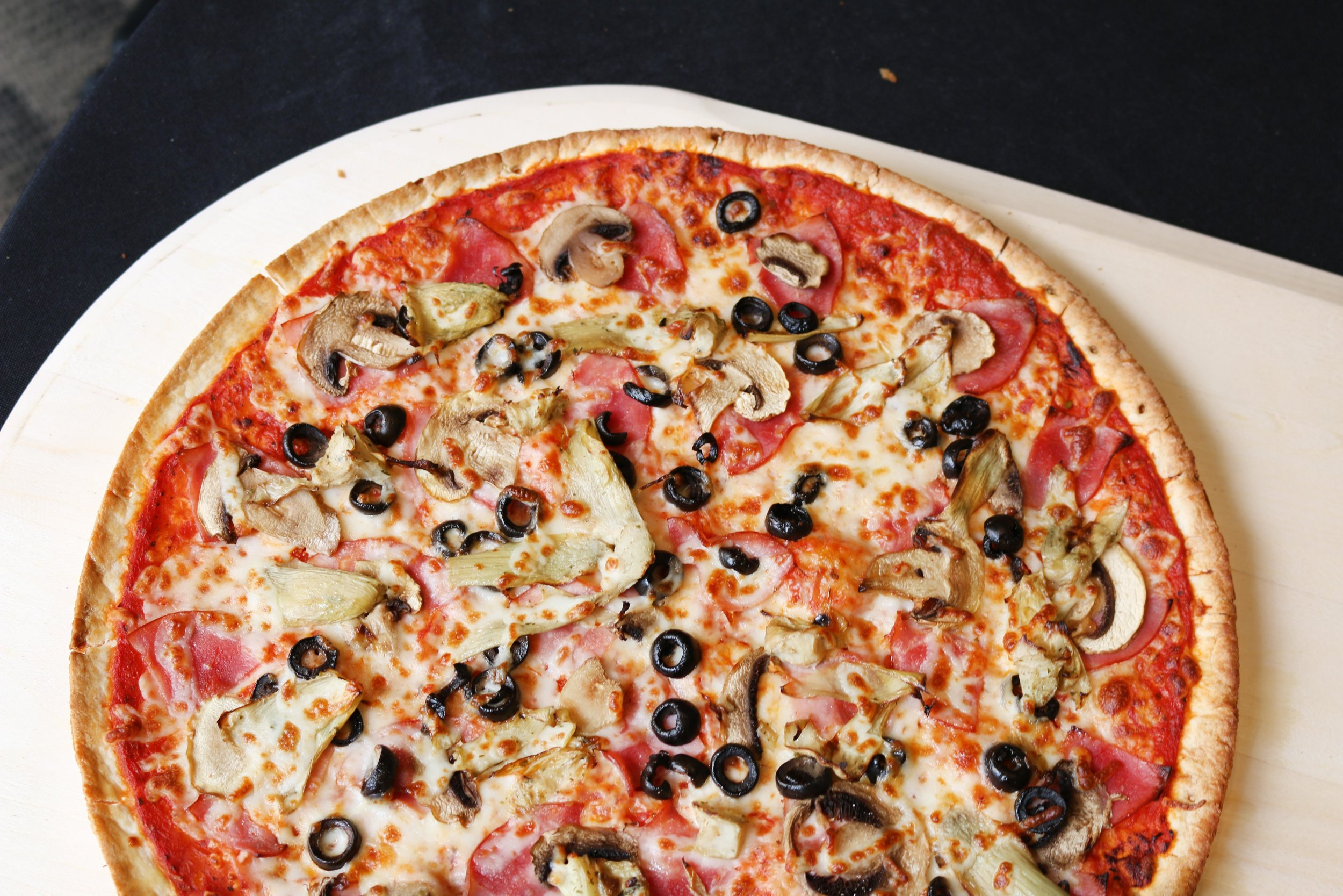 Thin Crust Capricciosa-  Thin layer of pizza dough, topped with ham, mushrooms, black olives, & artichokes. Try one today!