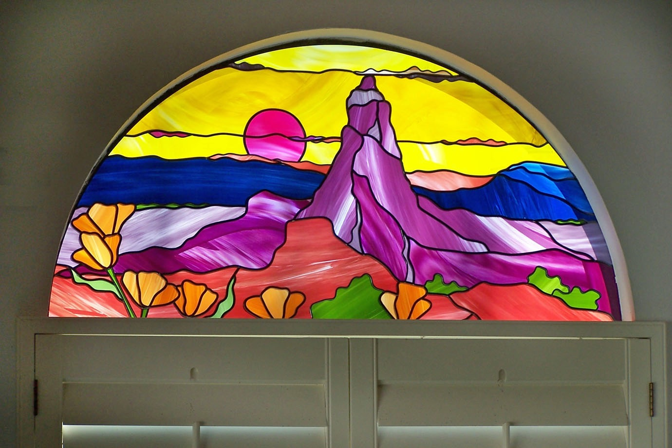 This half round transom is an Arizona desert sunset inspired placed in a home in Fallbrook.
