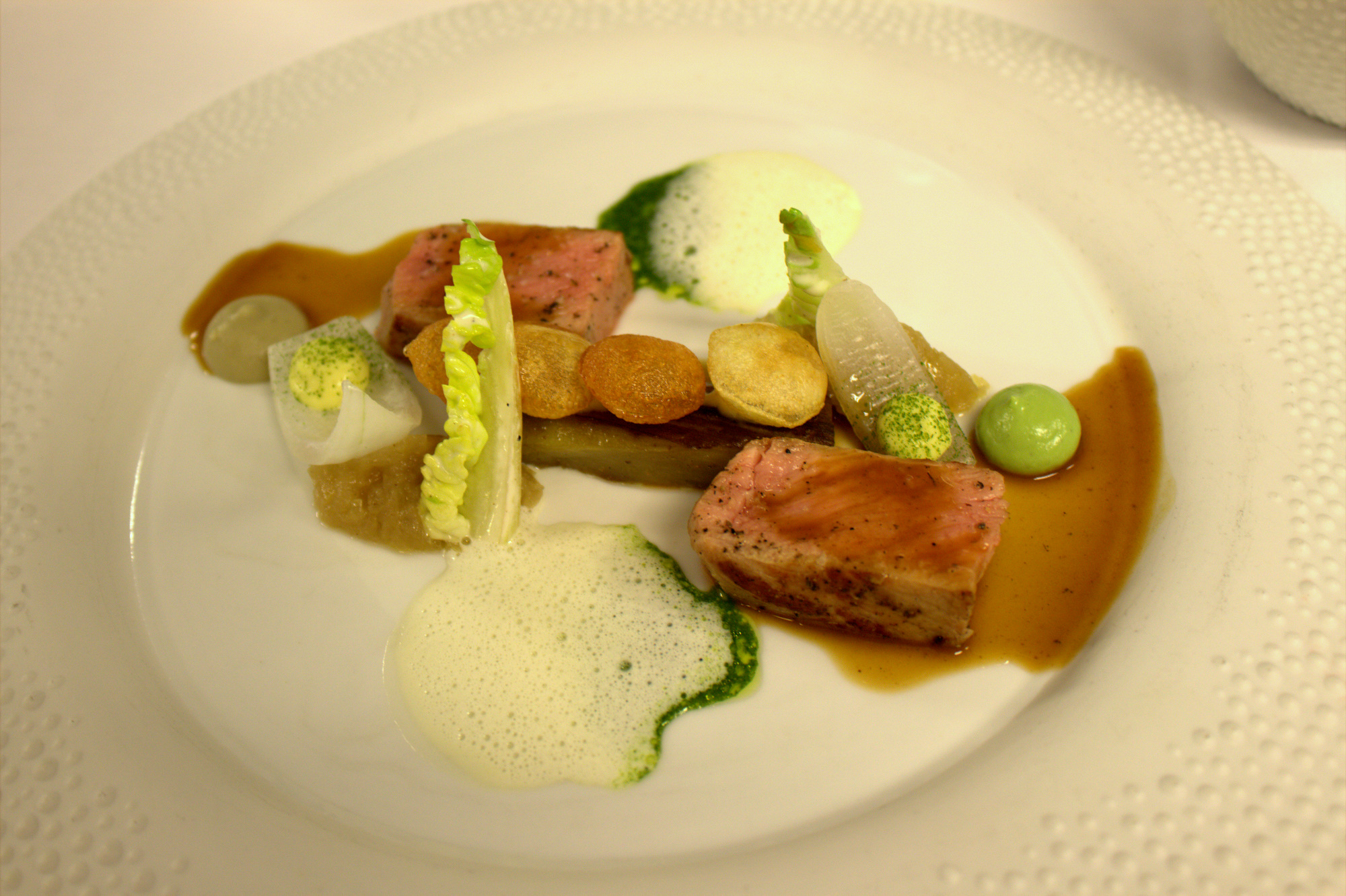 veal dish is served with sweet onion, aubergine, artichoke and a garlic distillation