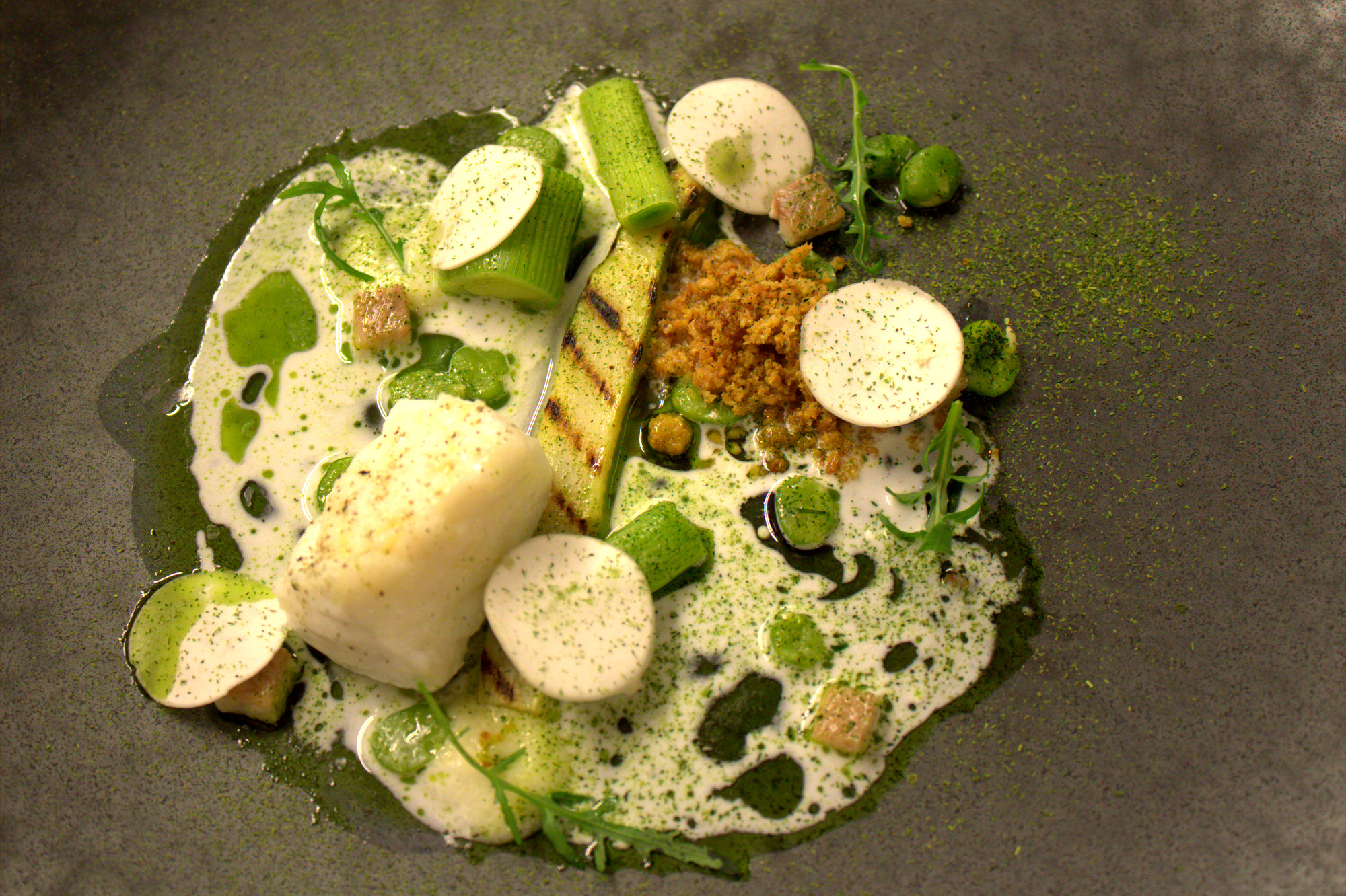 Cod with Parmesan crumble and cream, smoked eels, asparagus, peas, buttermilk and a rocket sauce