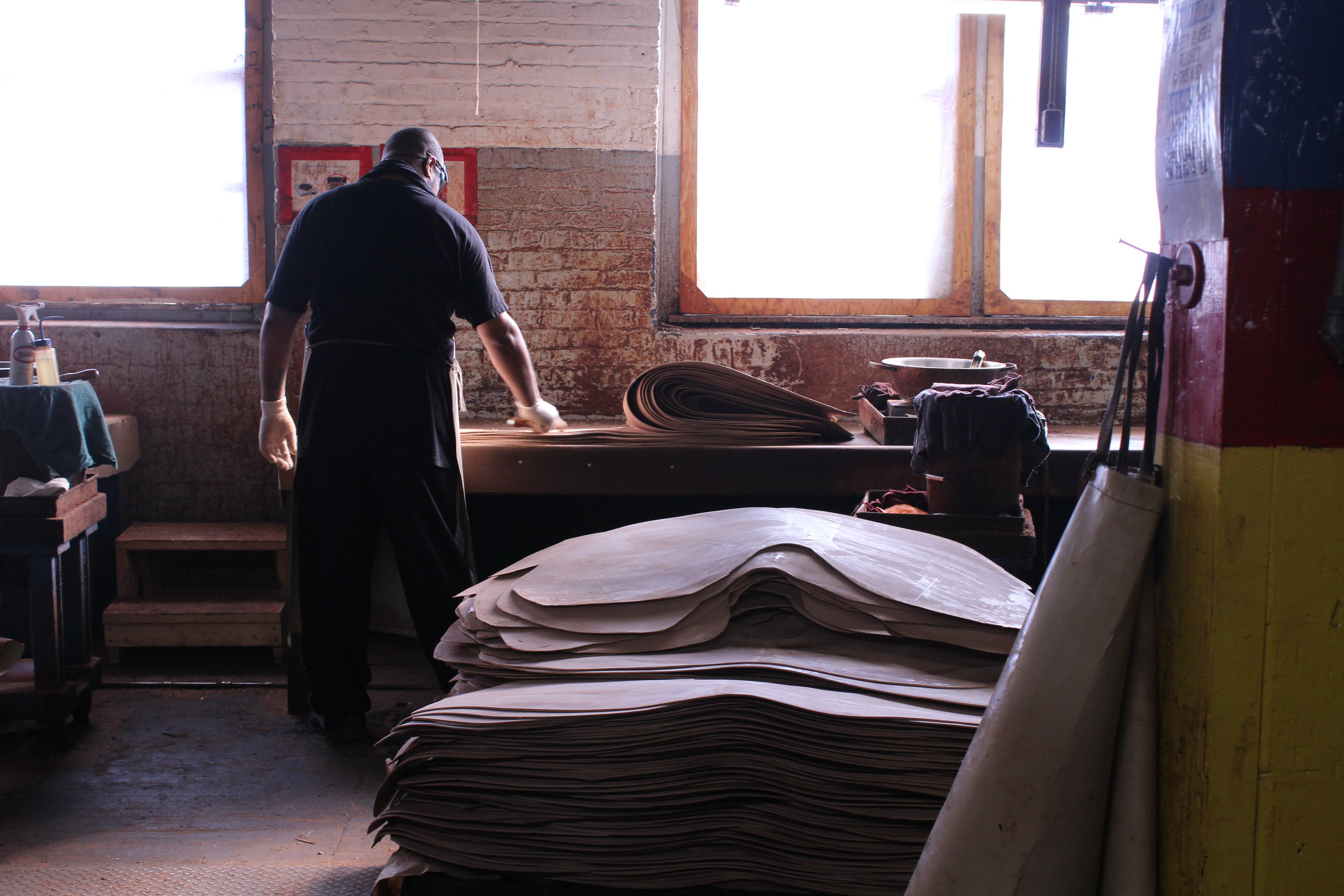 A Horween worker hand-coating the equine Genuine Shell Cordovan hides.