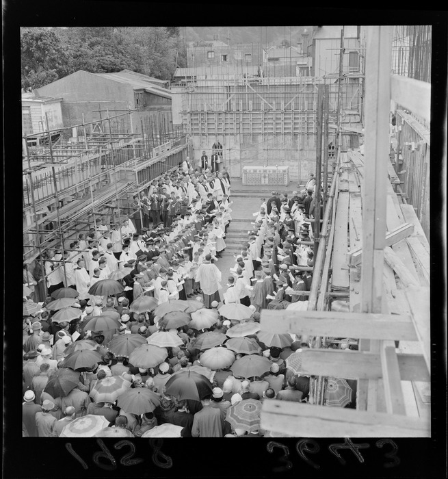 Service in the roofless Anglican Cathedral, Wellington, under construction, with altar, choir and umbrellas. Evening post (Newspaper. 1865-2002) :Photographic negatives and prints of the Evening Post newspaper. Ref: EP/1958/3643-F. Alexander Turnbull Library, Wellington, New Zealand.  /records/23259007