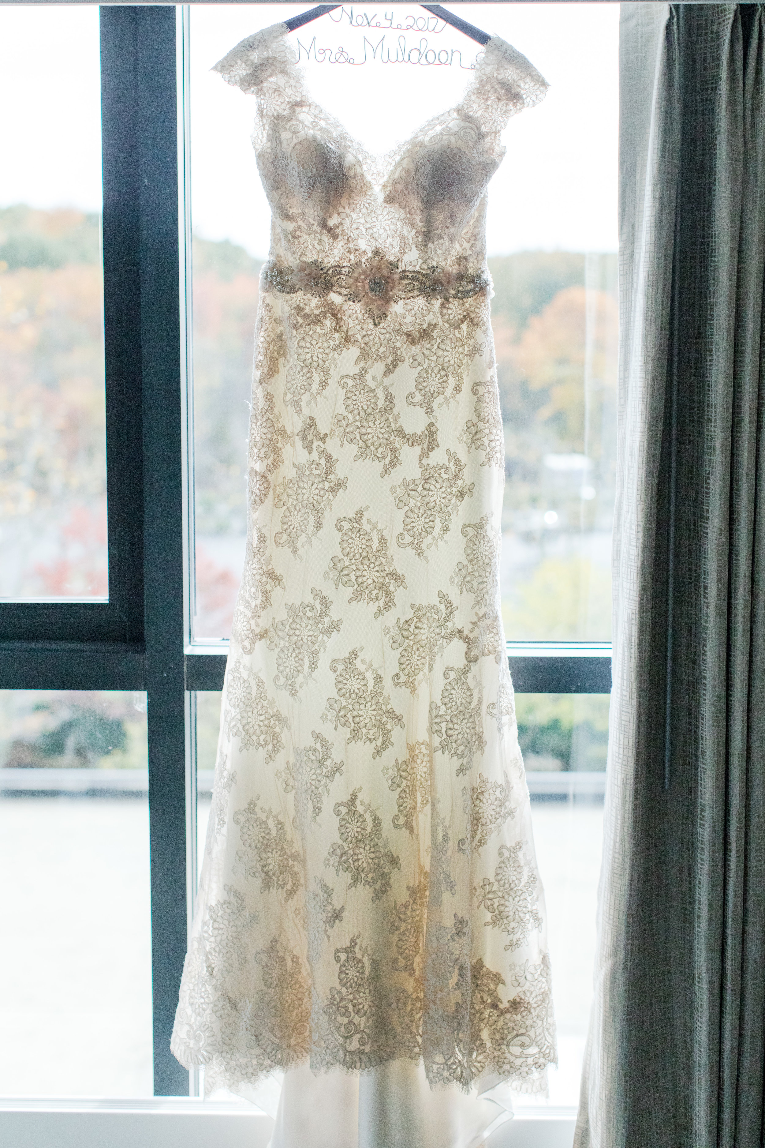 Fitted lace allure bridals wedding dress with beaded belt on mrs hanger photographed by jaye kogut