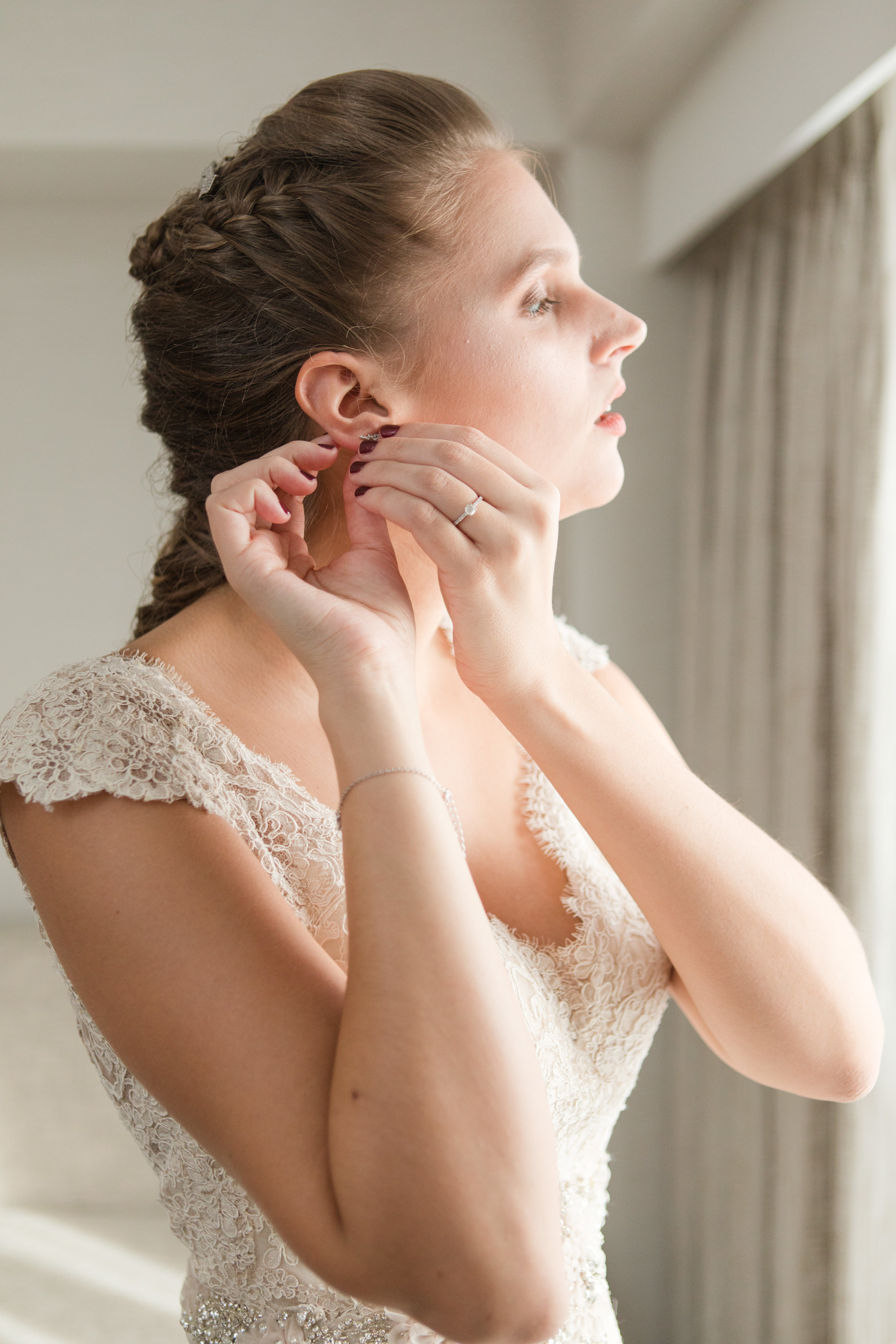 bride putting in earrings on wedding day in lace allure bridal gown photographed by jaye kogut