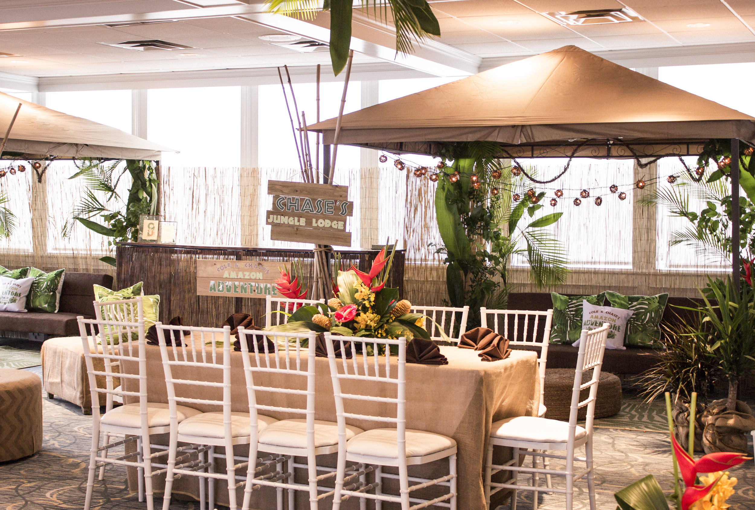 amazon jungle themed mitzvah kids lounge and seating with tropical centerpieces and cabana lounge