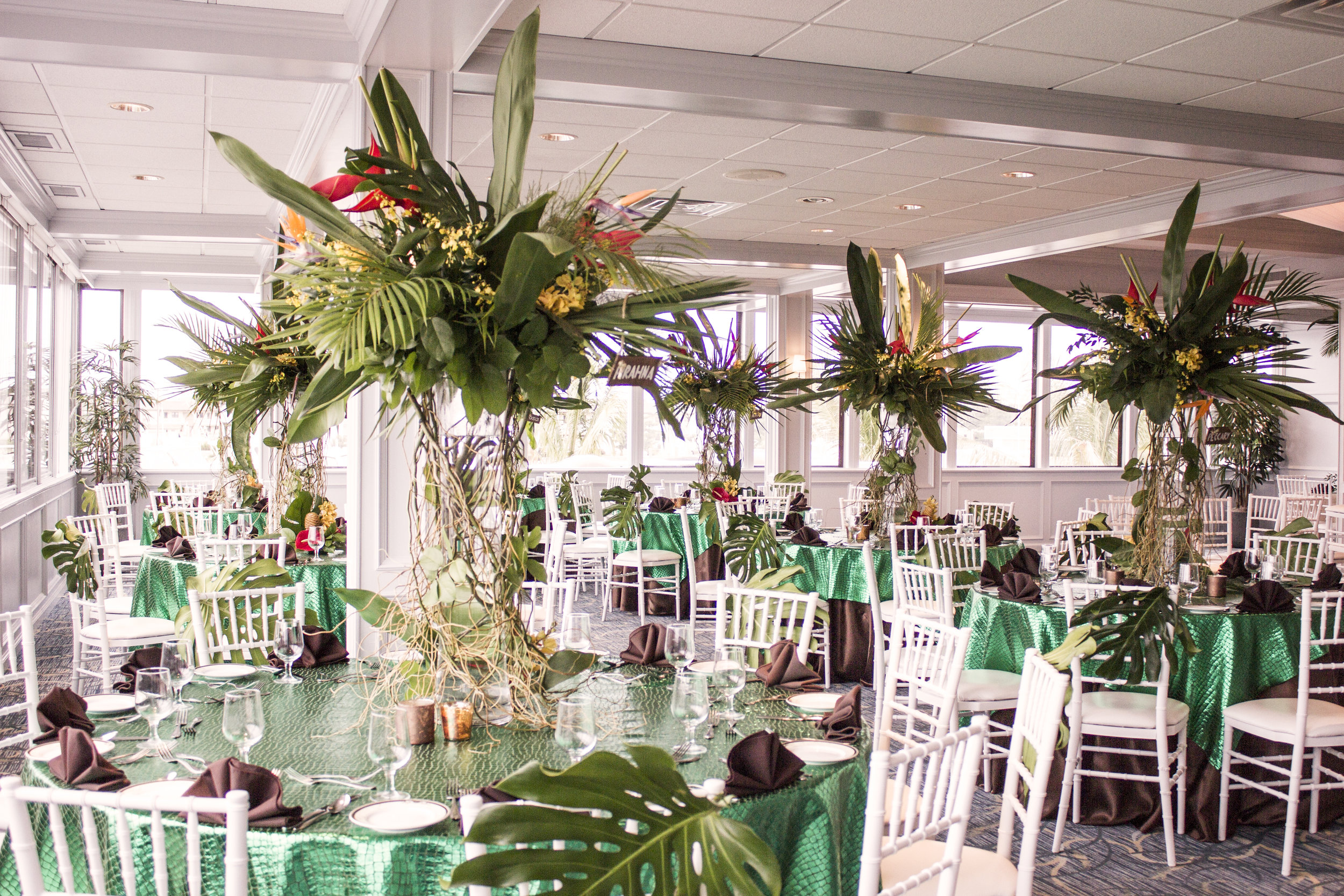 large tropical floral centerpiece for amazon jungle themed mitzvah with monstera leaf chair backs