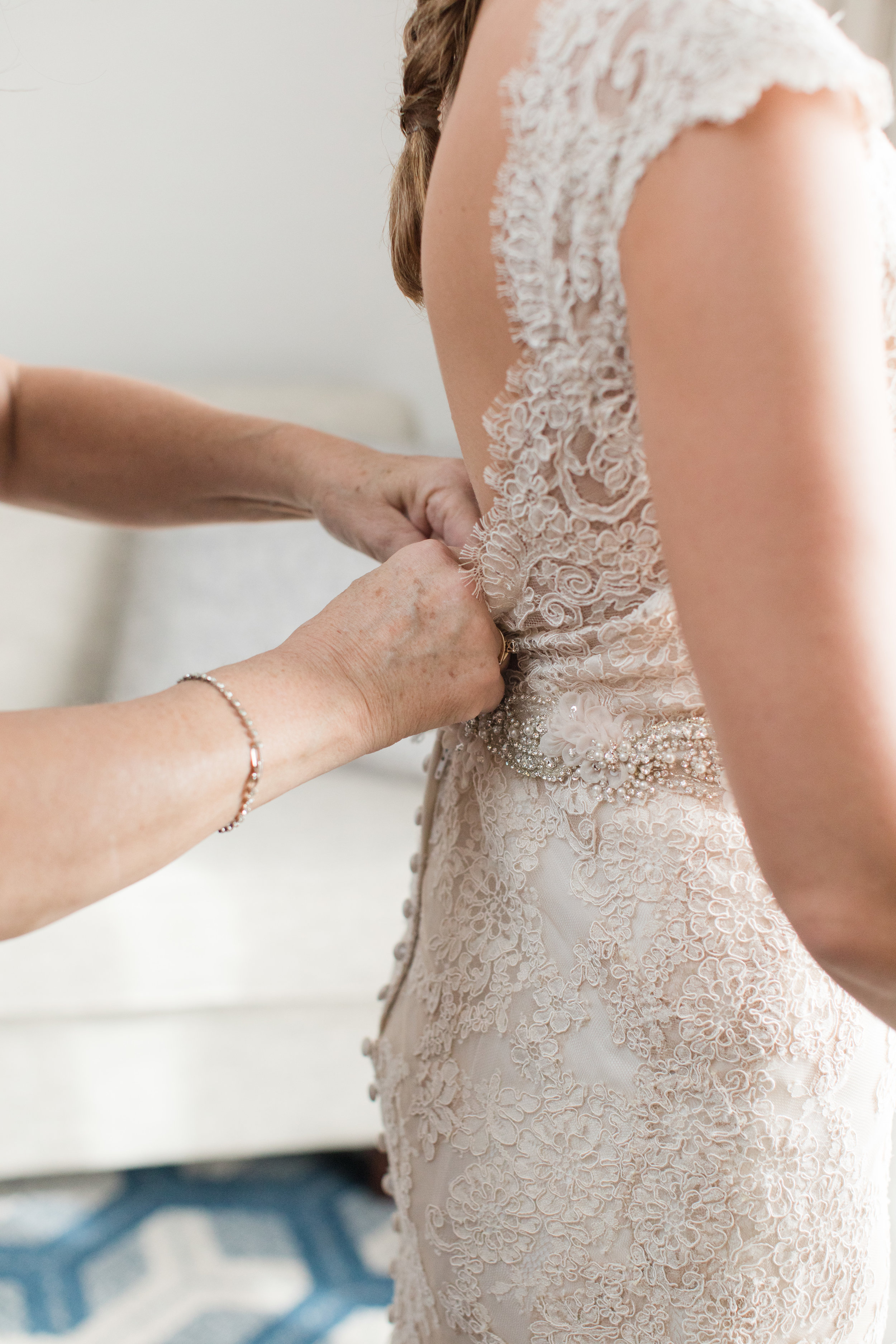 Mom buttoning brides lace dress with beaded belt