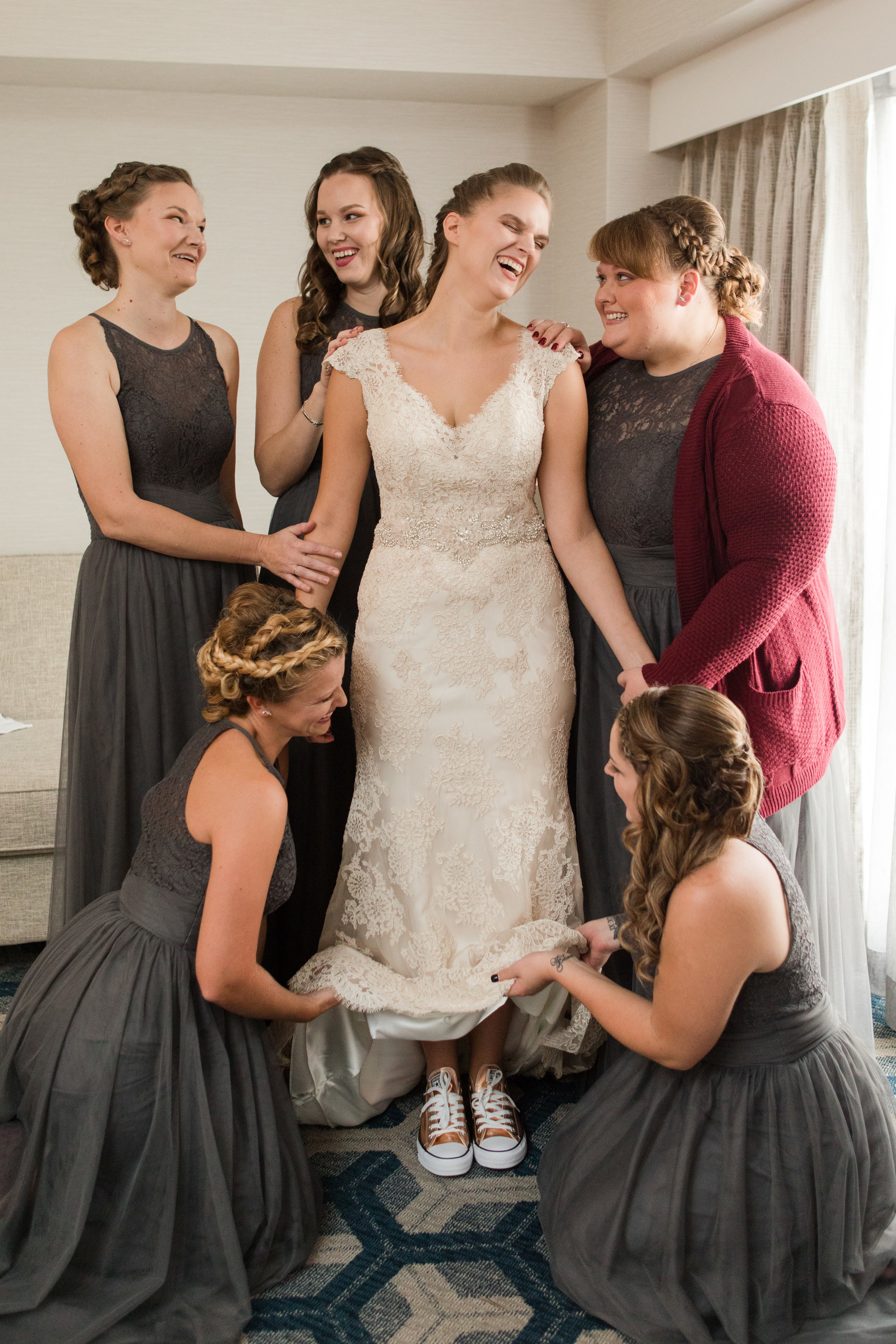 Bridesmaids help bride in lace gown into dress and rose gold converse wedding shoes