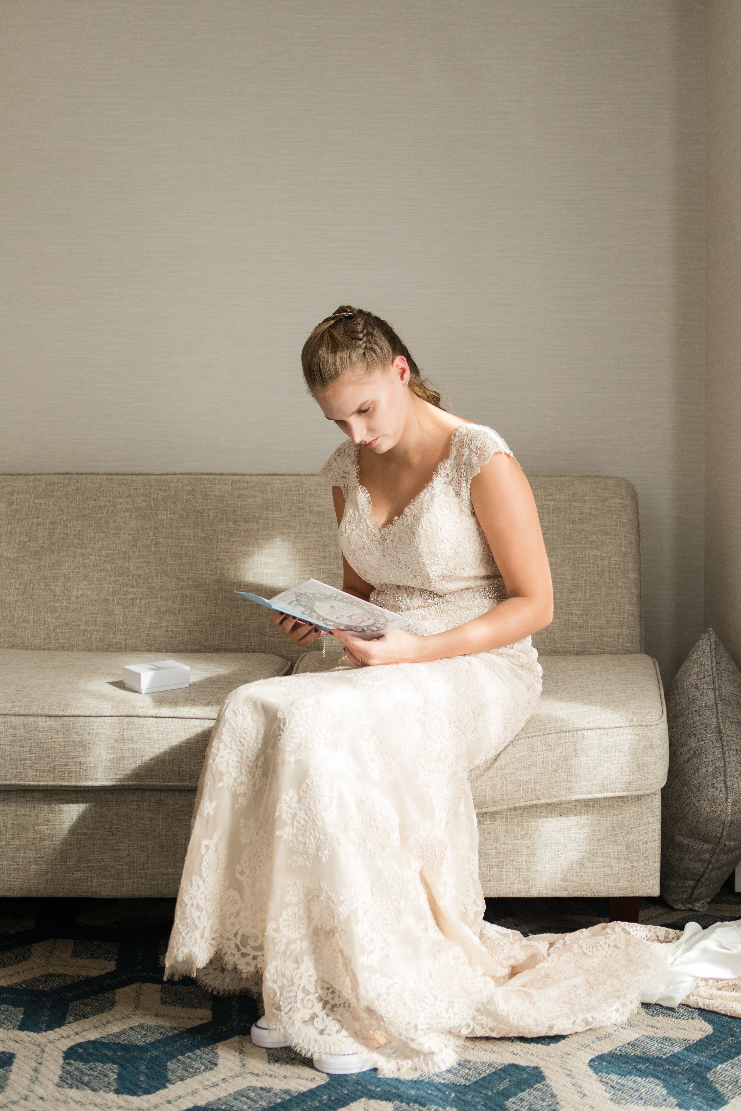 Bride in lace Allure Bridal gown reading wedding day card from groom at Sheraton Eatontown