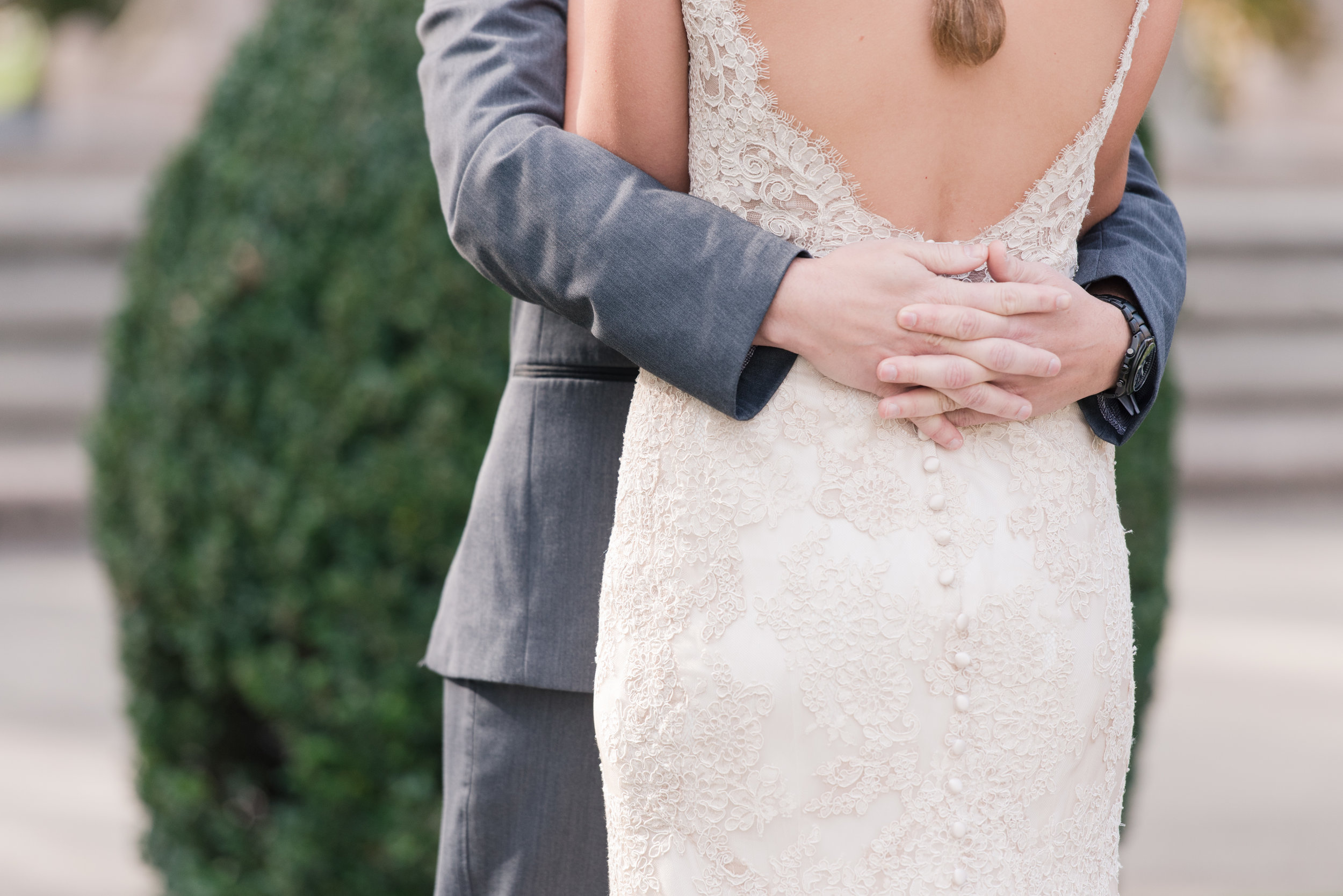 Groom hugs bride in lace Allure Bridal gown with low back and buttons
