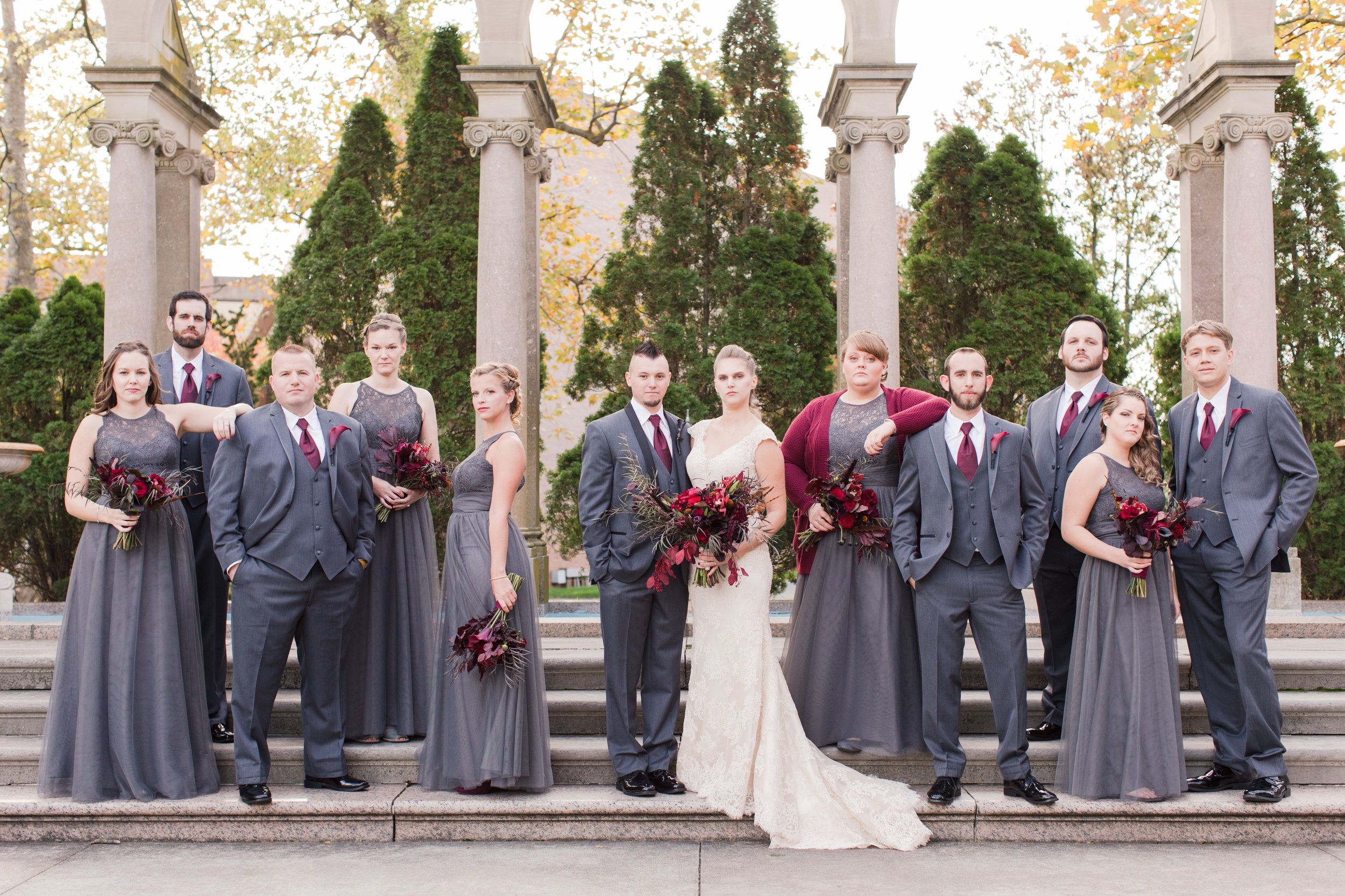 Bridal party in charcoal gray chiffon bridesmaid dresses with lace and groomsmen in black and gray tuxes pose with bride in allure bridal lace wedding gown and groom at monmouth university in the fall
