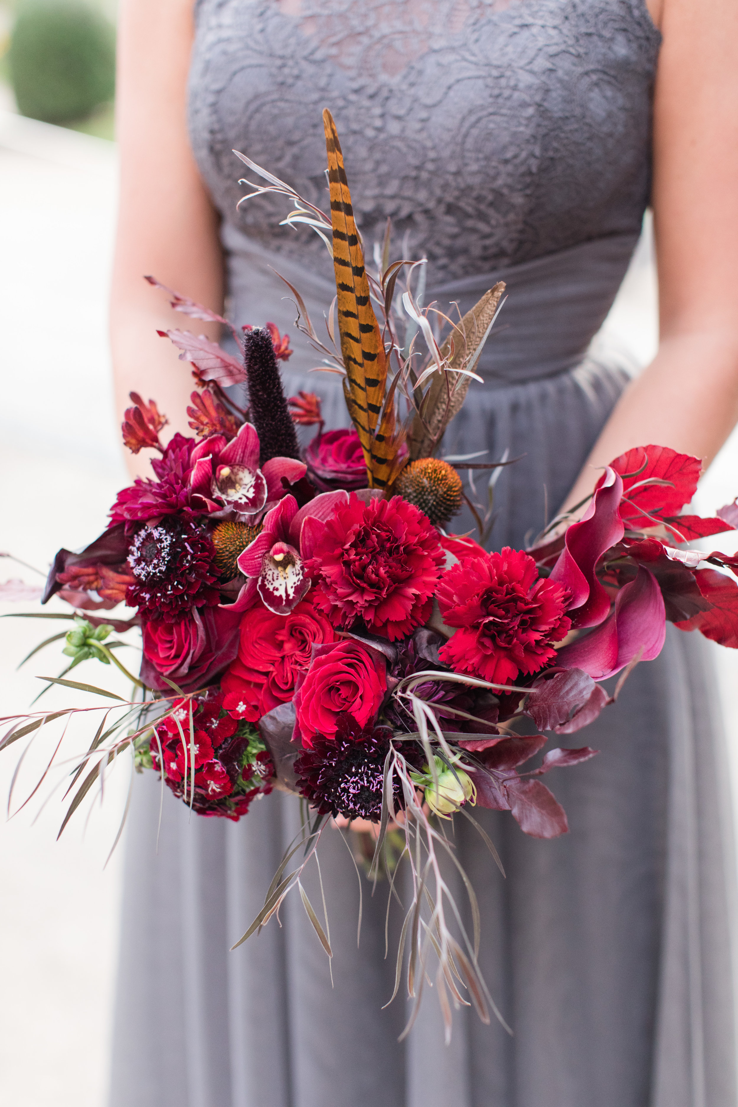 Dark red fall bridesmaid bouquet with feather