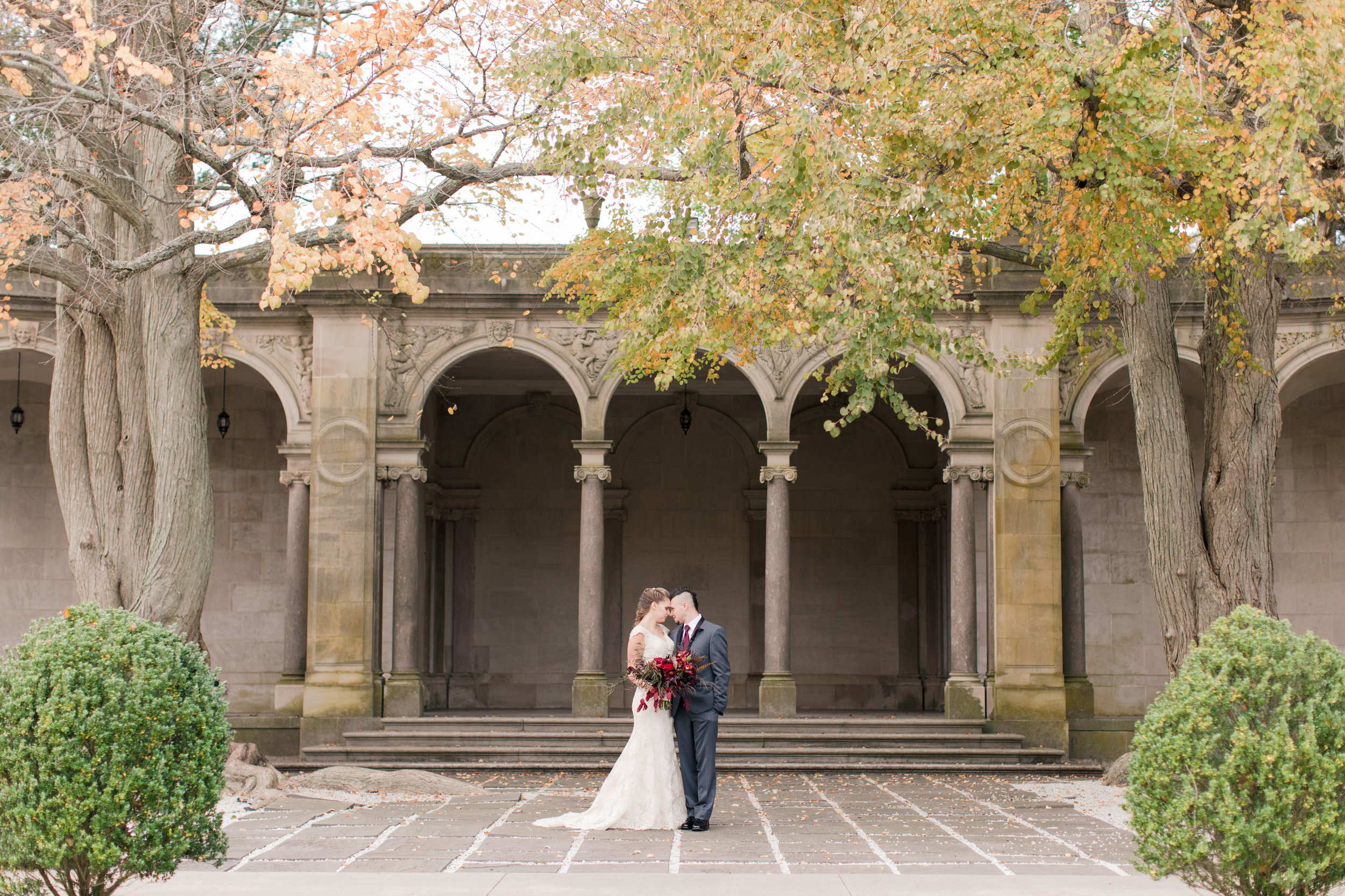 bride in lace allure gown with dark red fall bridal bouquet poses with groom at Monmouth University