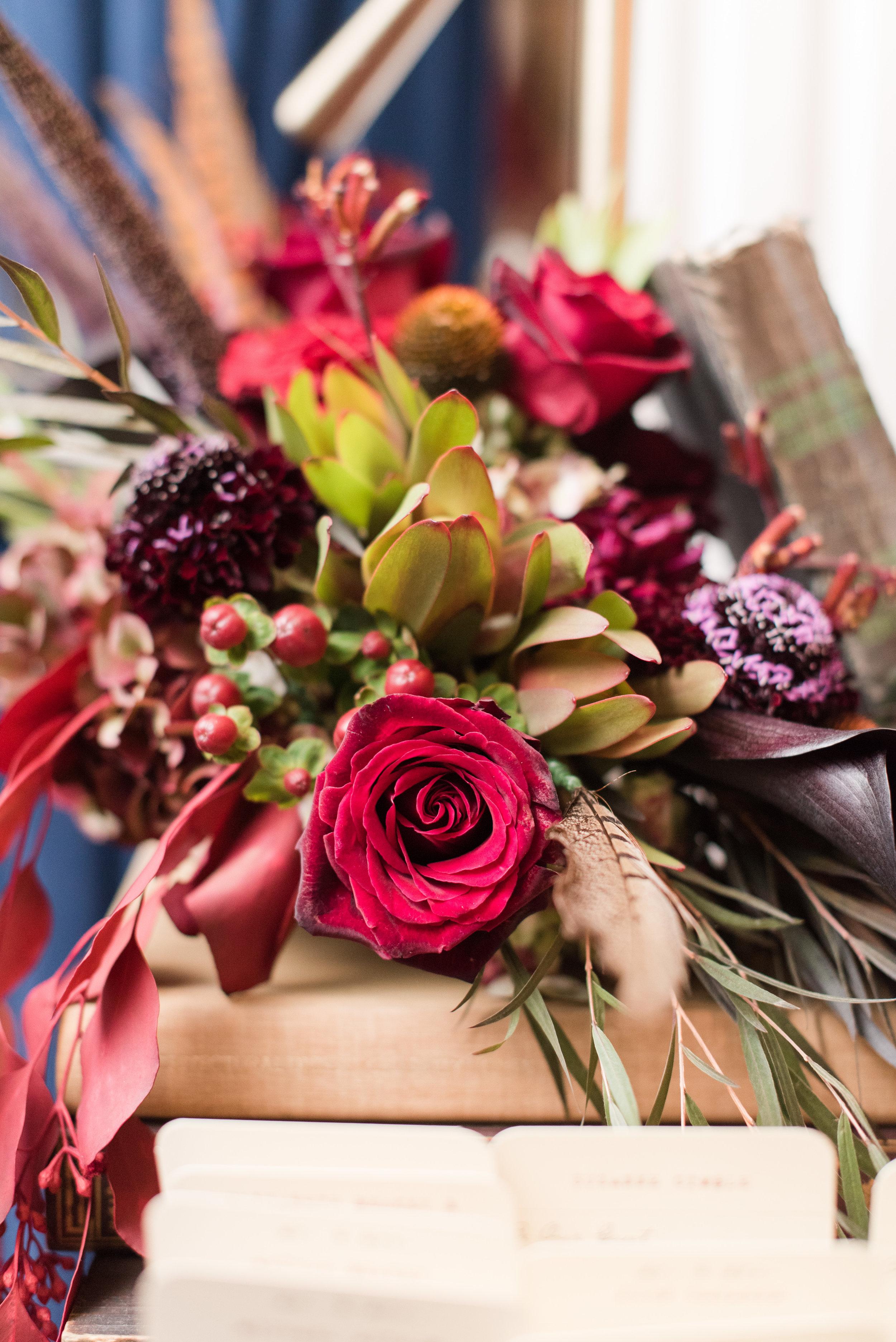 Dark red seasonal fall flower arrangement atop books
