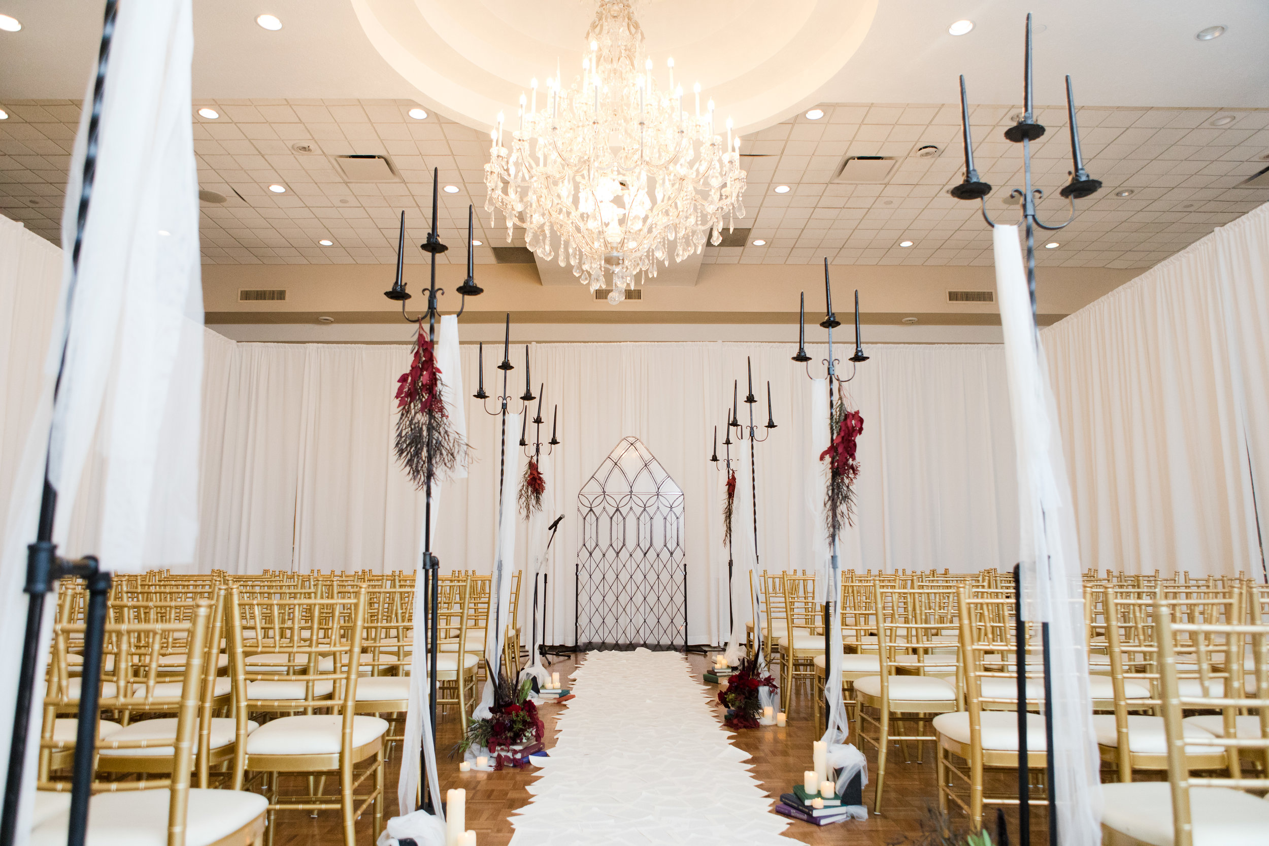 Beauty and the Beast inspired ceremony at Buona Sera Palazzo with castle window ceremony backdrop and book page aisle runner