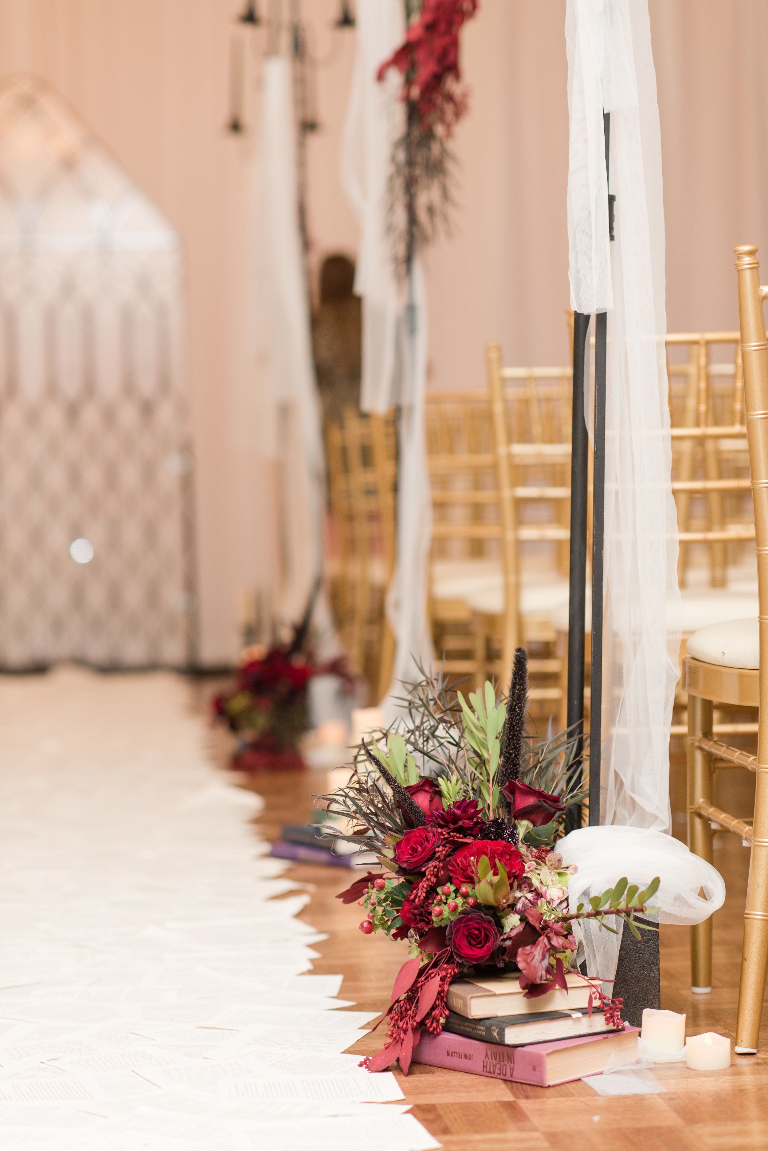 Seasonal fall floral arrangements atop of books aisle decor for library inspired wedding with book page aisle runner