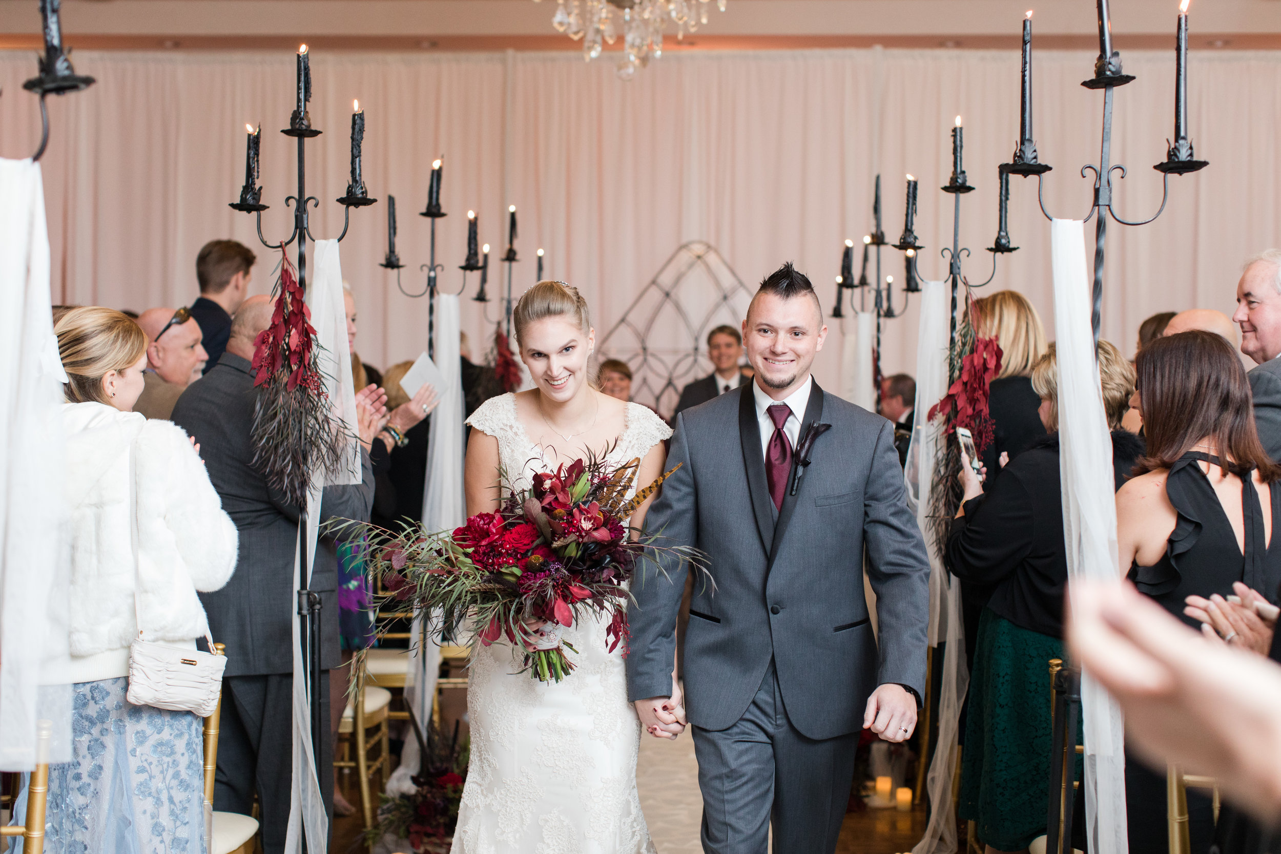 Bride and groom exit the beauty and the beast inspired ceremony at a fall library inspired wedding at Buona Sera Palazzo dark red and black fall bridal bouquet