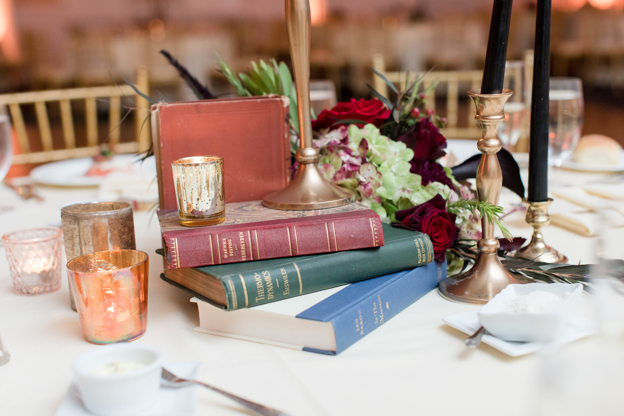 vintage book centerpieces with flowers and candles for library inspired fall wedding at buona sera palazzo