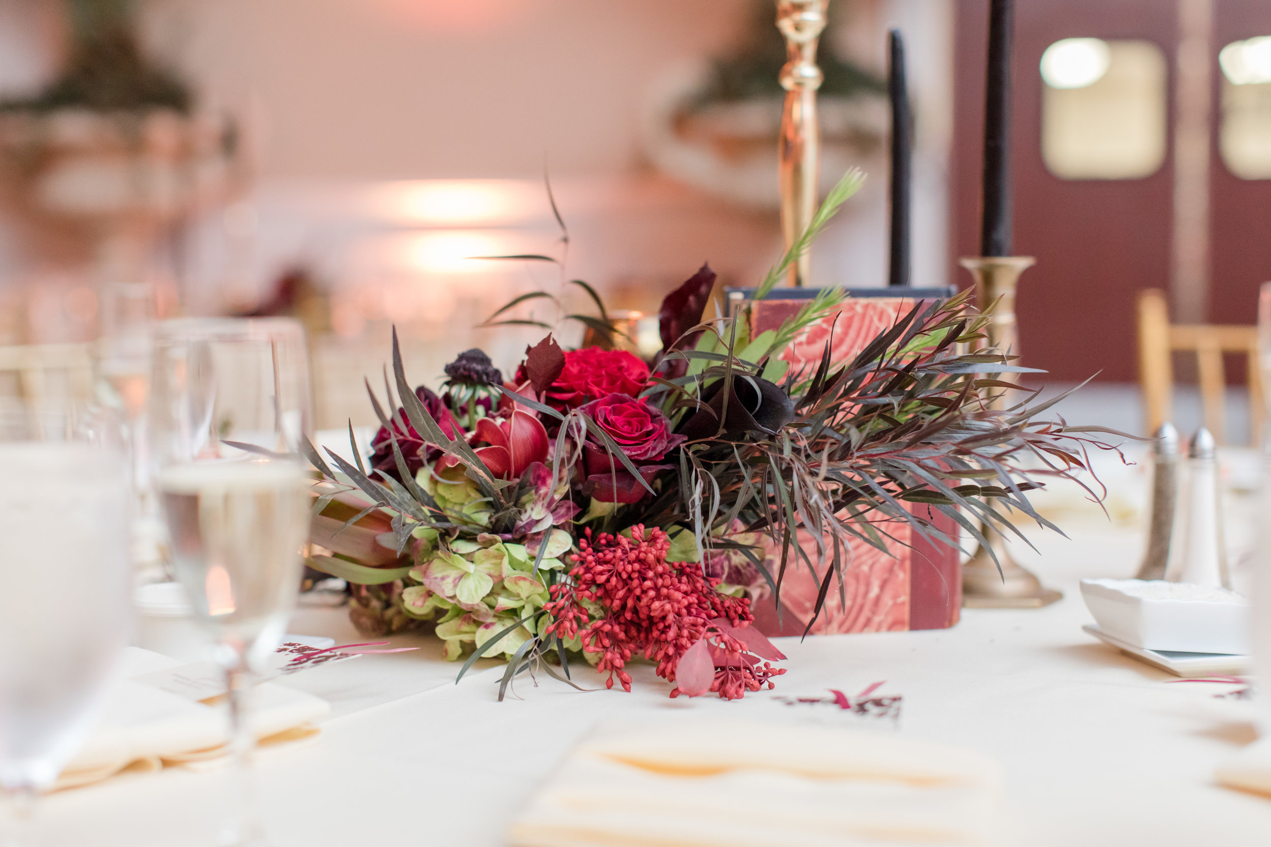 vintage book and fall floral centerpiece with candles at library inspired fall wedding at buona sera palazzo