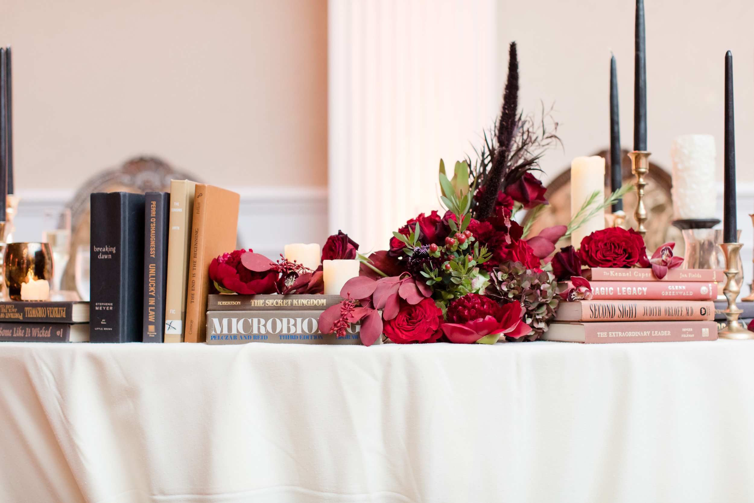 library inspired fall wedding sweetheart table with vintage books dark red fall flowers and black taper candles