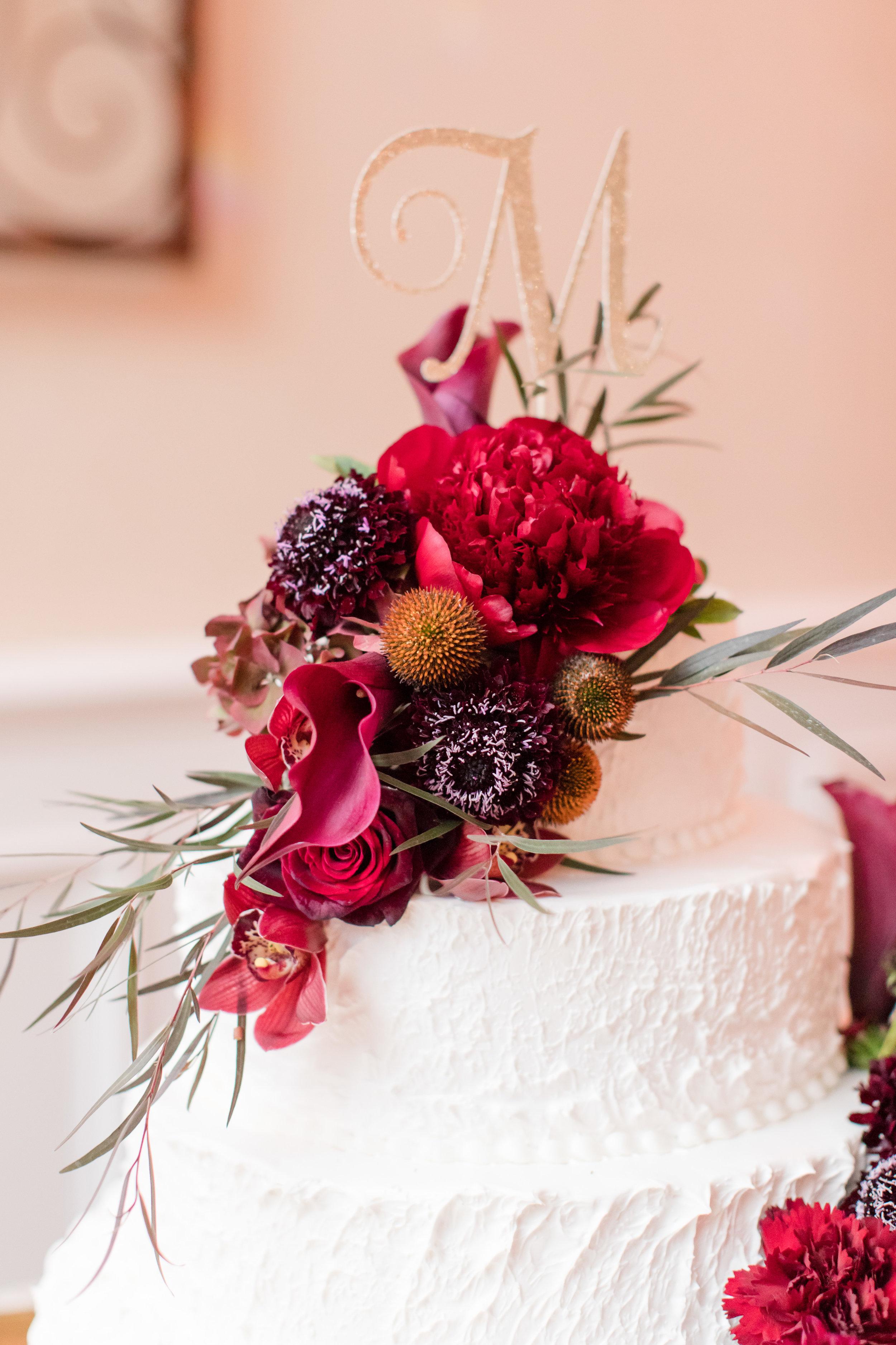 White wedding cake with fresh flower topper dark red flowers and gold glitter monogram