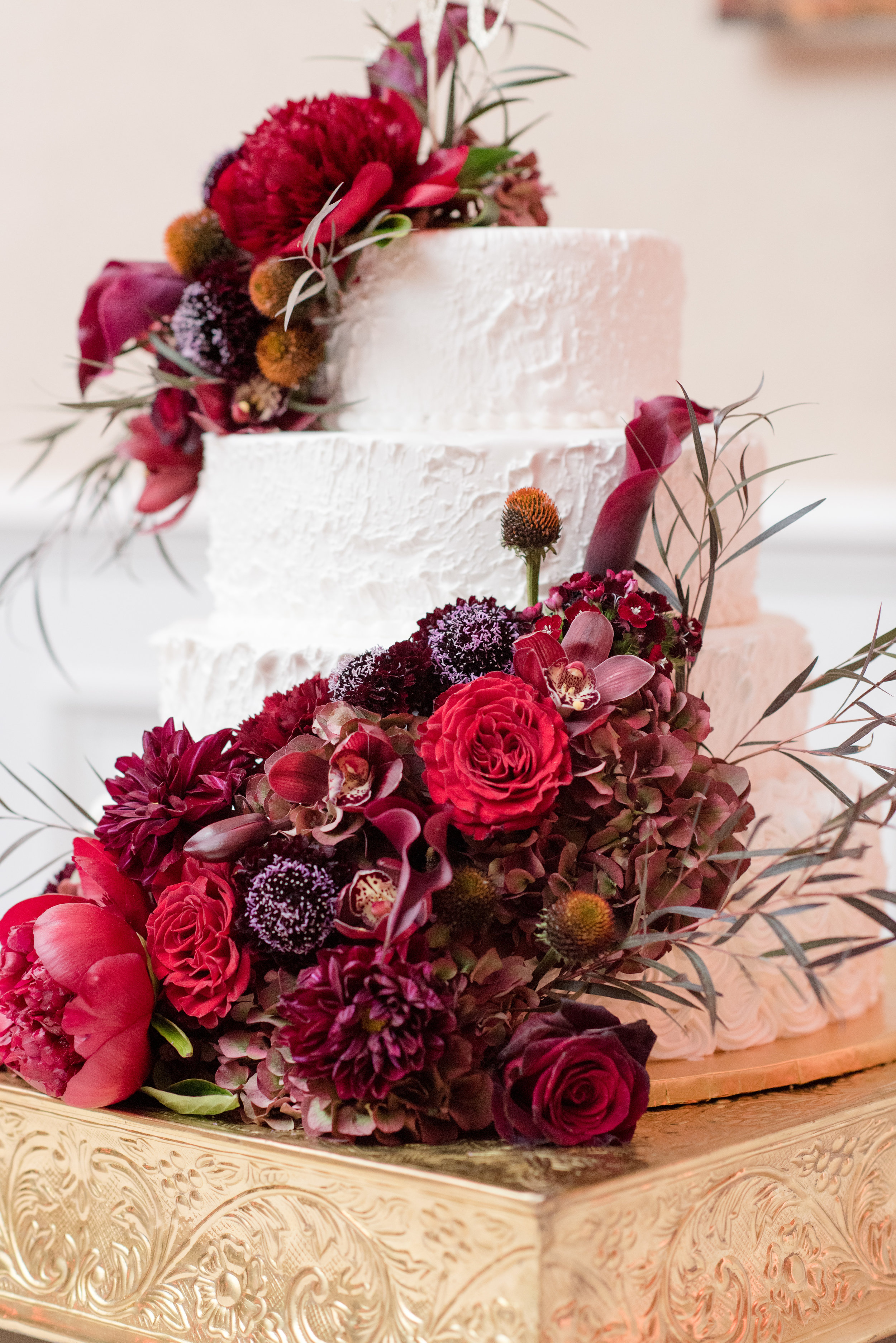 White wedding cake with dark red black and purple fall flowers
