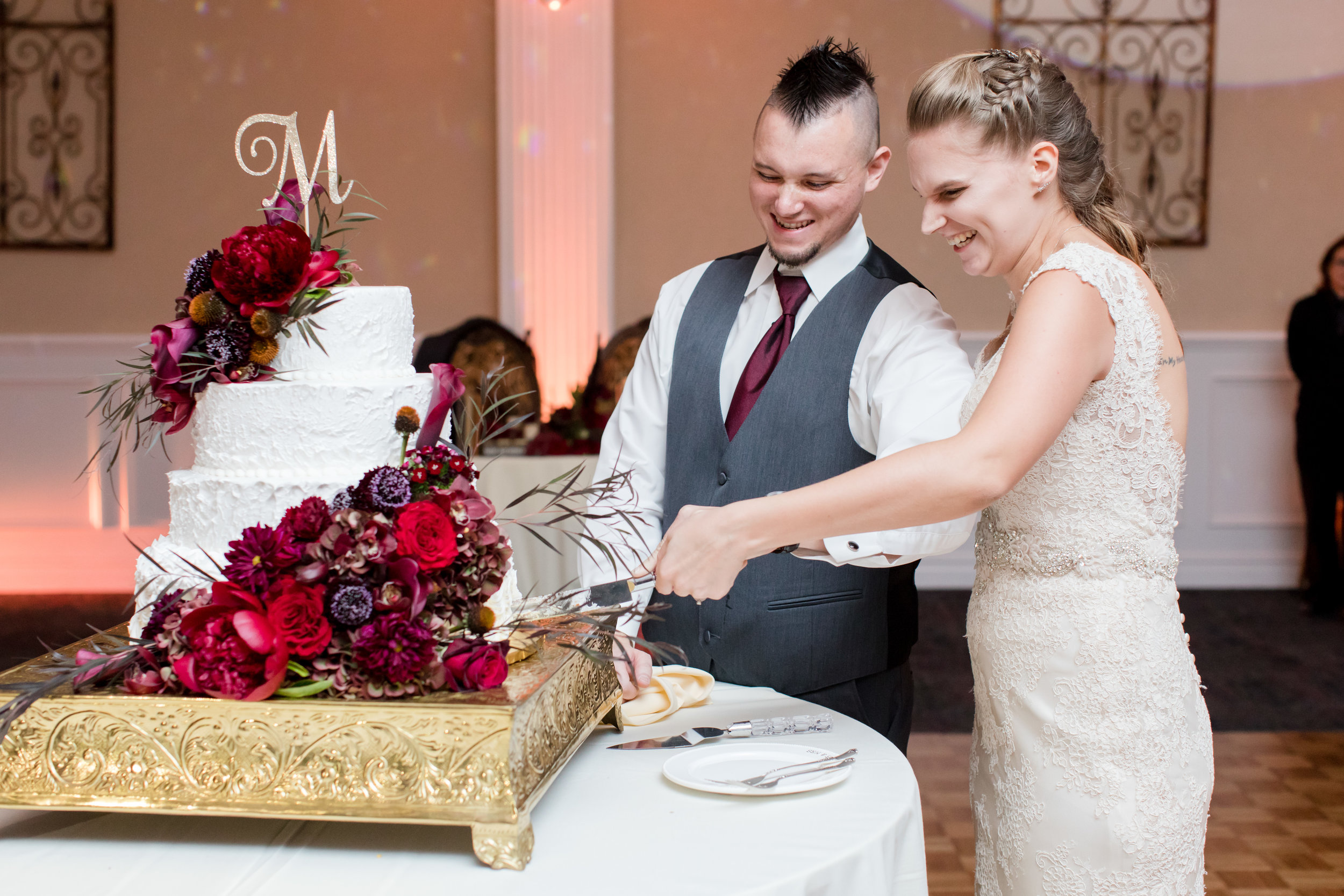 White wedding cake with dark fall flowers and gold glitter cake topper