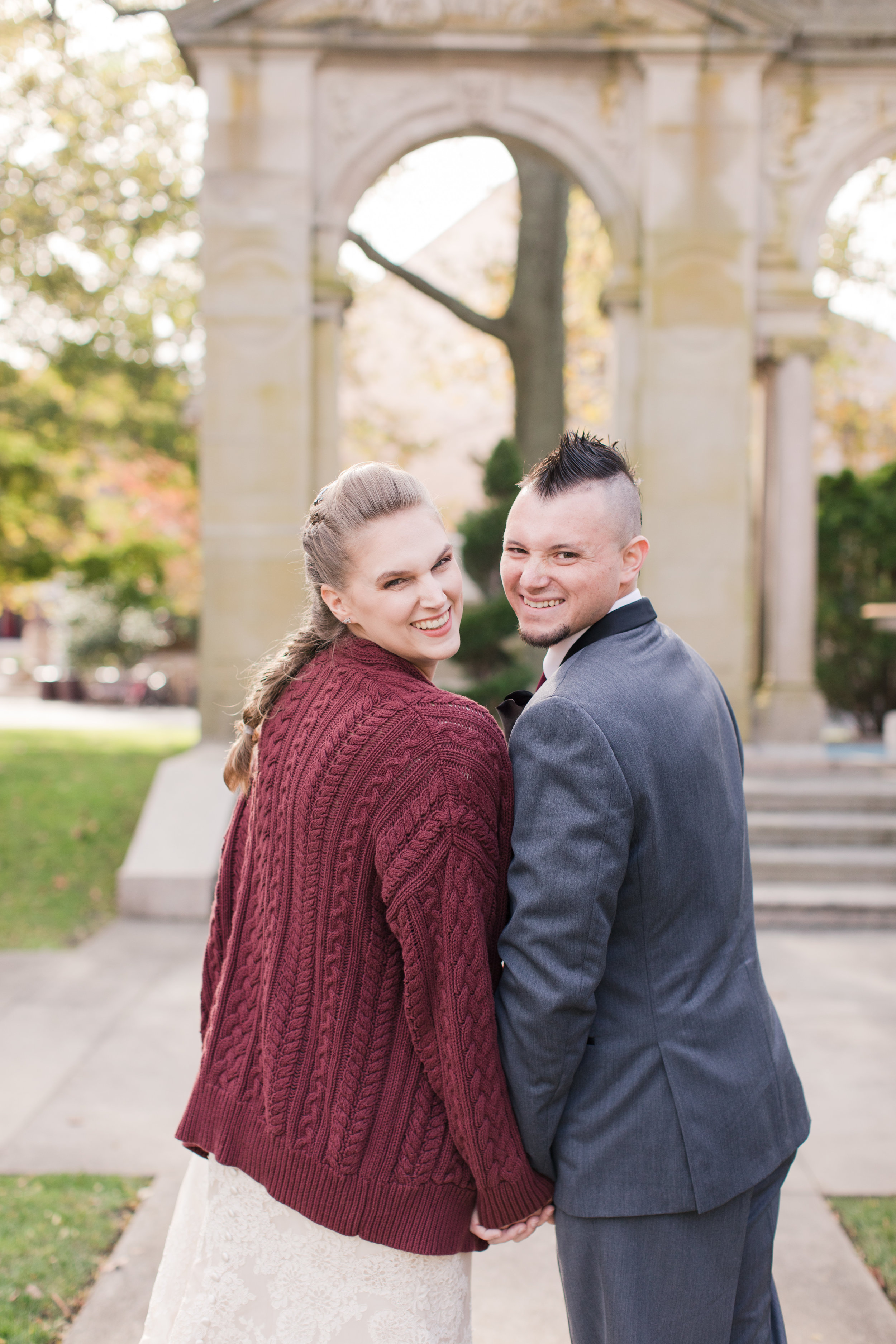 bride poses with groom in chunky knit sweater at fall new jersey wedding
