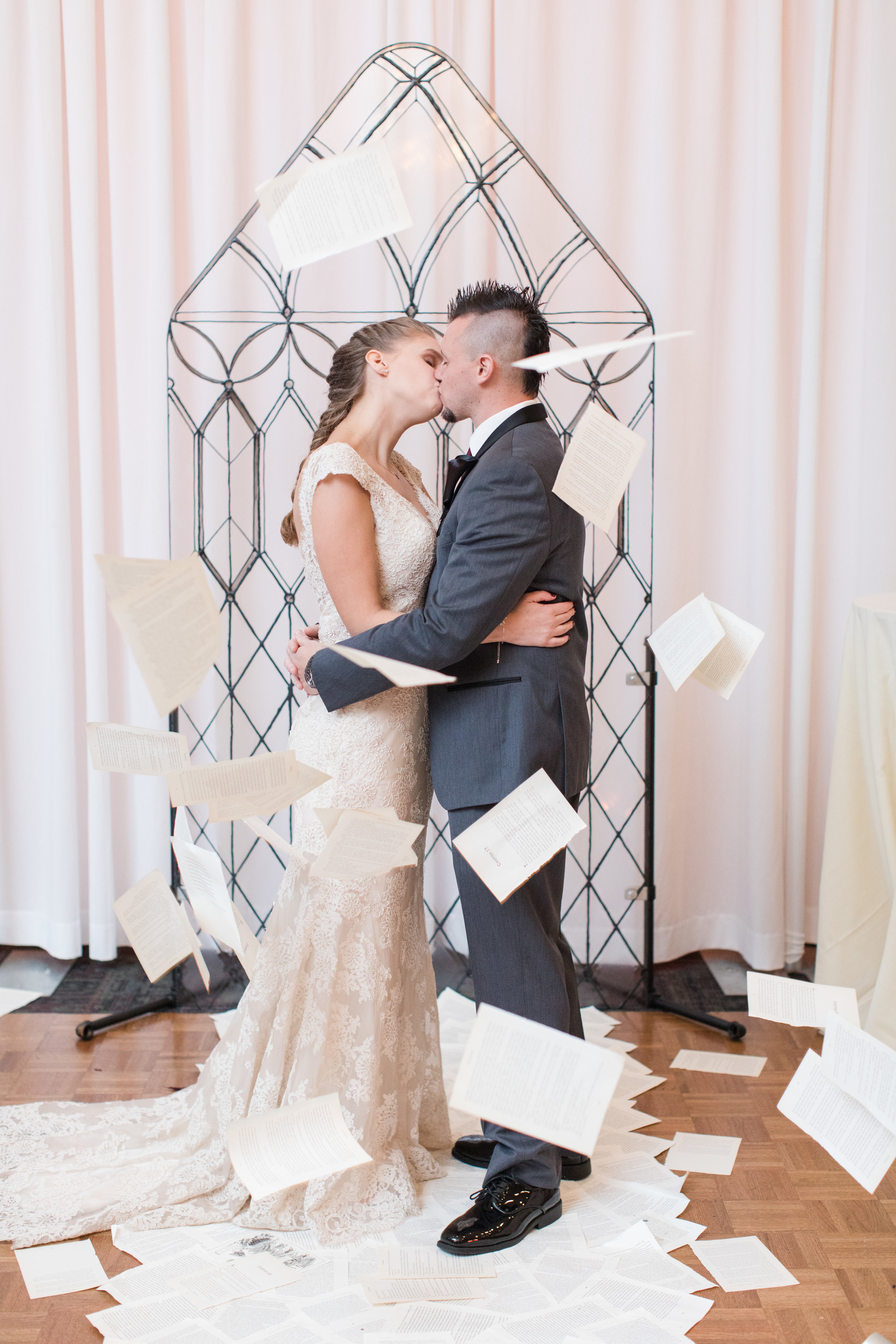 bride in allure bridal lace gown stands atop book page aisle runner in front of castle window ceremony backdrop with groom in dark gray suit as book pages fall over top of them