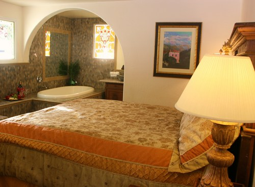 KING/QUEEN SUITE  Two room corner suite with a king and queen bed an archway dividing them.