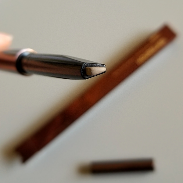 The Hourglass Arch Brow Sculpting Pencil features a unique triangle tip.