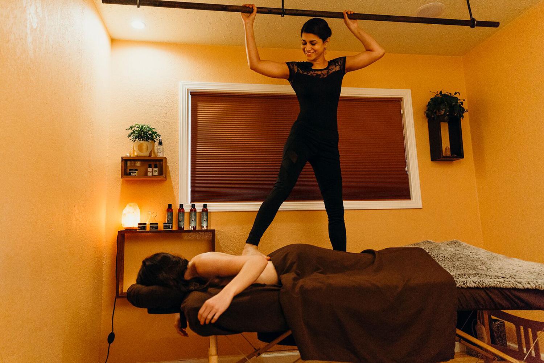 A therapist performs an Ashiatsu Massage on a client.