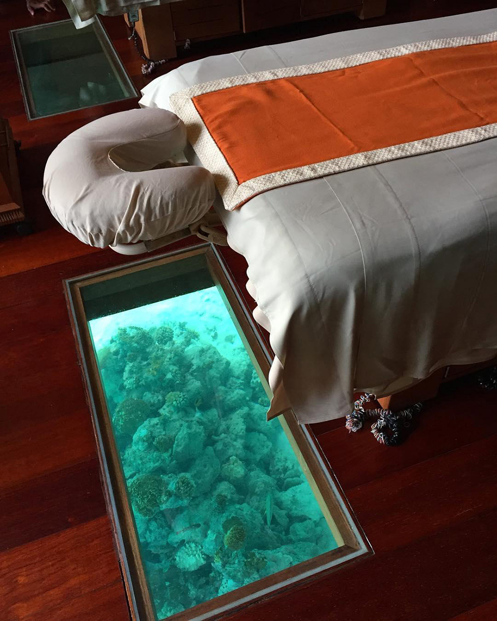 Guests receiving treatments in the Fare Miti Overwater Spa Suite can observe fish swimming underneath glass panels.