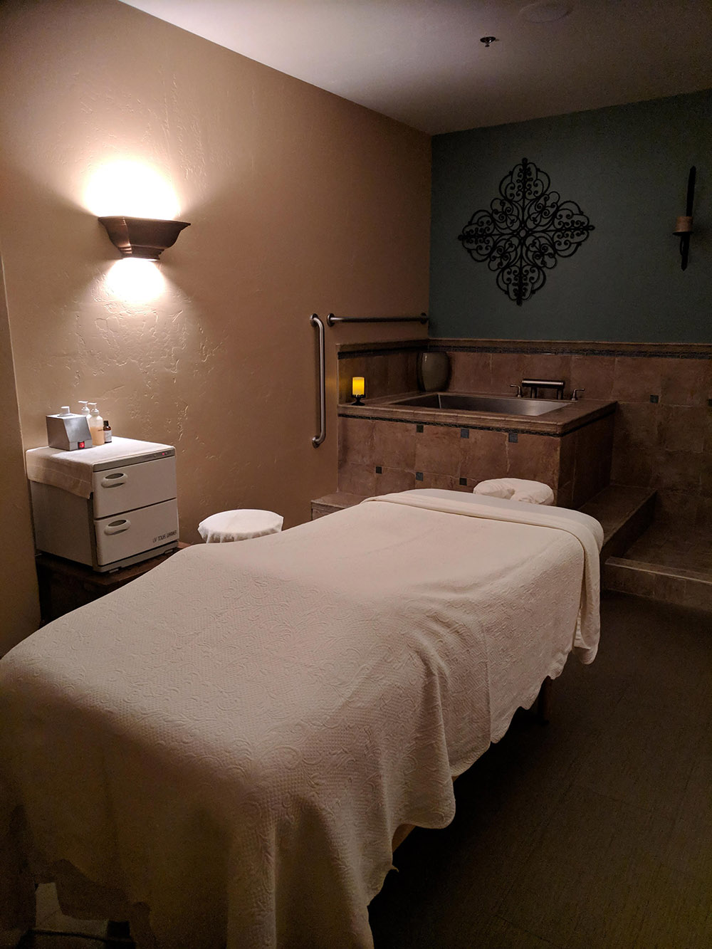 A massage treatment room in soft earth tones equipped with a soaking tub.