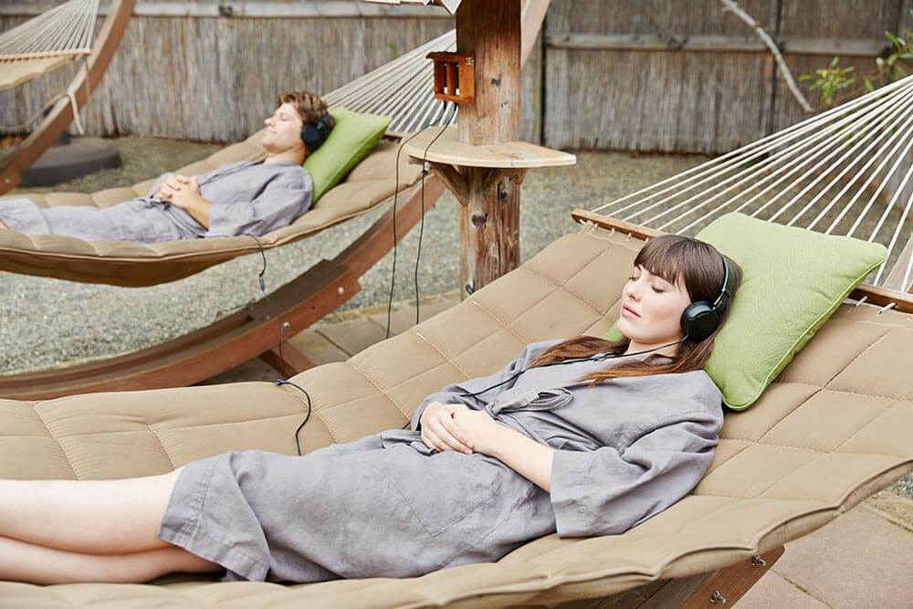 Osmosis guests relax in a hammock while enjoying sound therapy beside the salmon creek.
