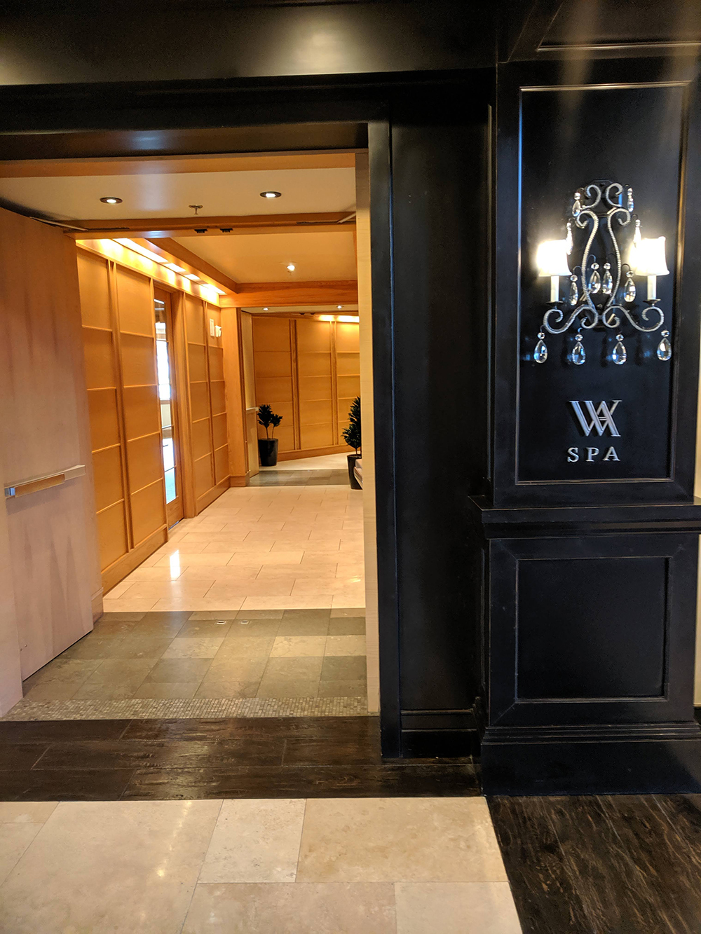 A hallway of warm wood welcomes guests to the spa.